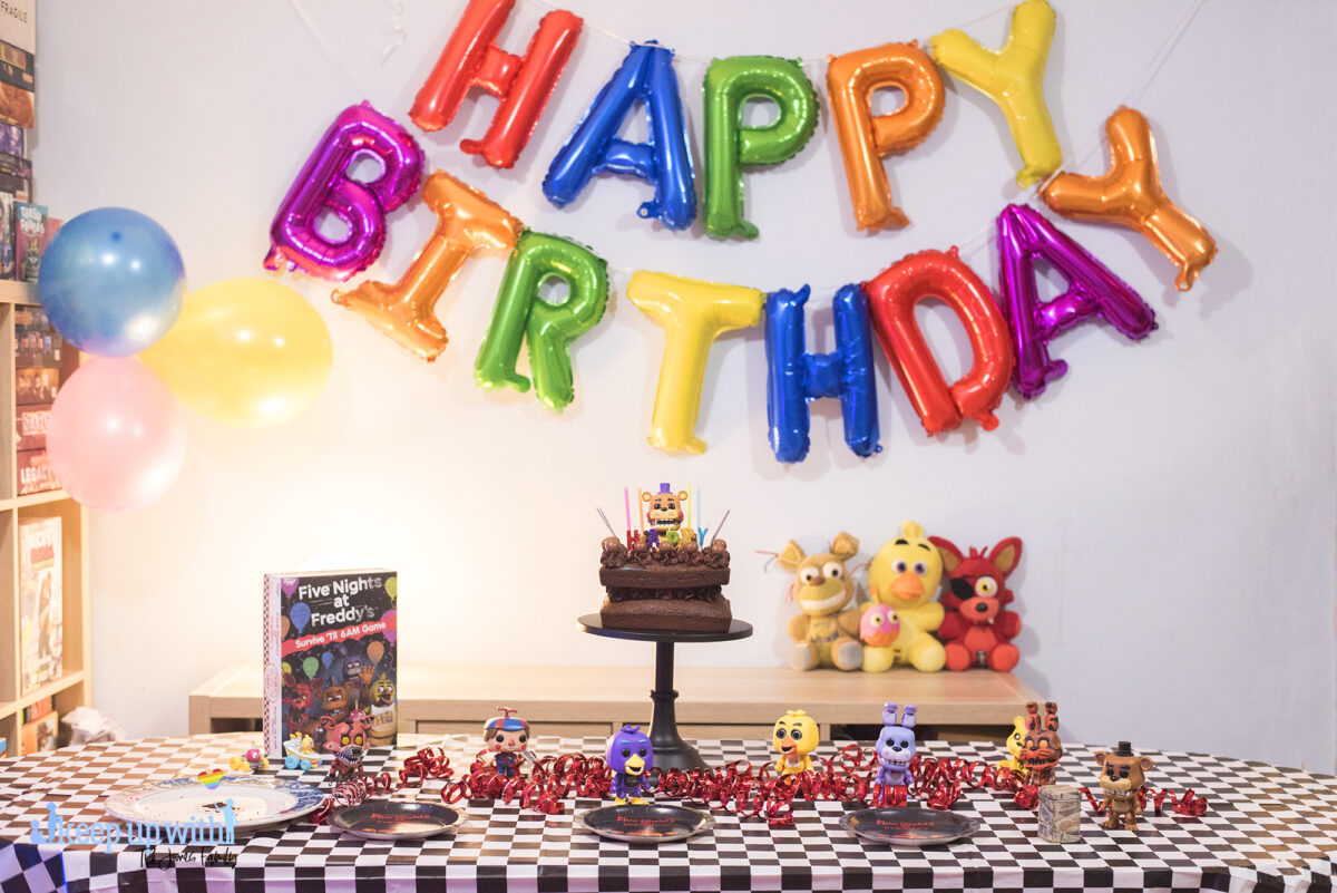 How to throw a Five Nights at Freddy's Party. Image shows a party table covered in a black checkered tablecloth, happy birthday spelled out in rainbow coloured balloons as a garland across the wall, three FNAF plushies; Foxy, Chica and Plushtrap sat on the sideboard and a chocolate cake on a black cake pedestal with a Funko Pop Vinyl Rockstar Freddy on top of it. The FNAF board game is on the table with more Funko figures - chica, jack-o-bonnie, black light chica and balloon boy.