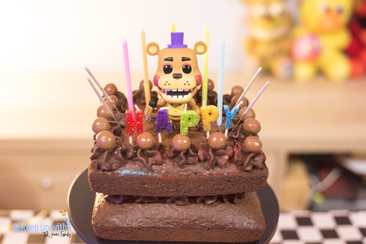 """Image shows a homemade square chocolate cake decorated with candles in different colours saying """"happy:. There are chocolate icing swirls set with maltesers on top and there are sparklers ready to be lit sticking out of the cake.  In the middle of the cake sits a Funko Pop Vinyl sigure of Freddy Fazbear."""
