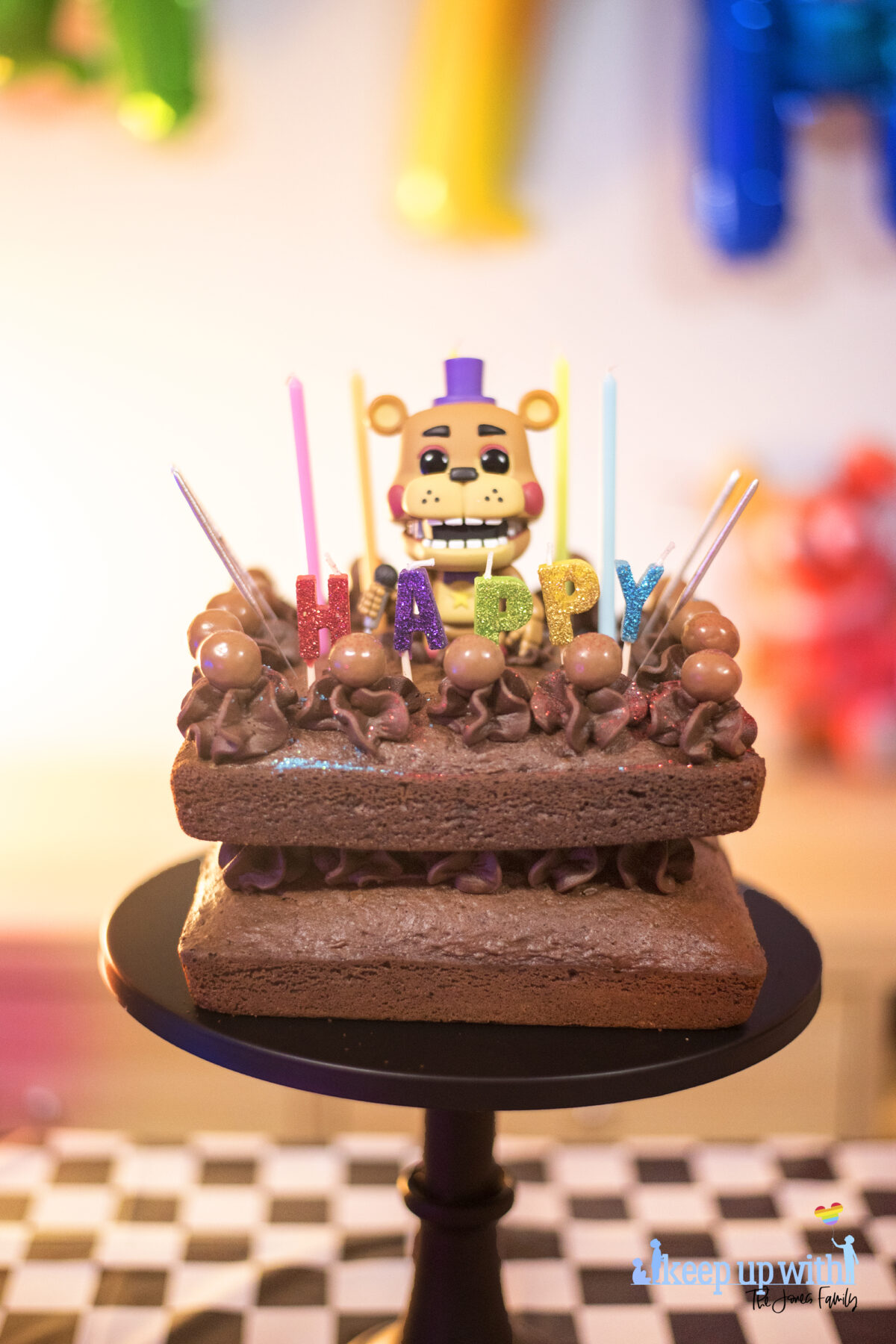 """Image shows a homemade square chocolate cake decorated with candles in different colours saying """"happy:. There are chocolate icing swirls set with maltesers on top and there are sparklers ready to be lit sticking out of the cake.  In the middle of the cake sits a Funko Pop Vinyl sigure of Freddy Fazbear. Image by keep up with the jones family."""
