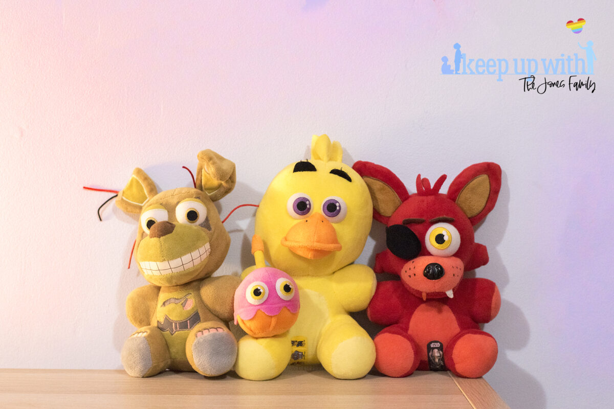 Image shows three Five Nights at Freddy's large plush toys. Foxy, Chica   Mr Cupcake and Springtrap. They are sat on a wooden sideboard against a pale blue wall. Image by keep up with the jones family.