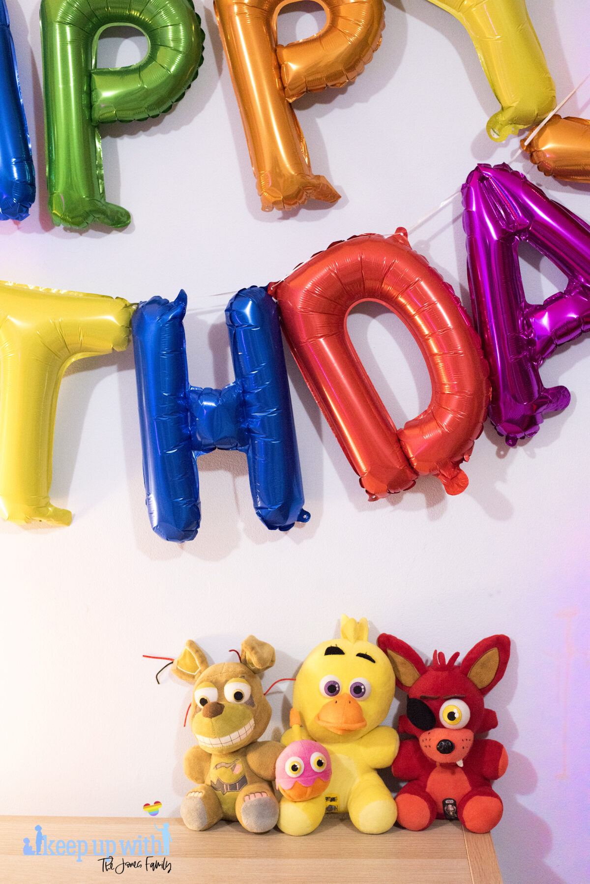 Image shows three Five Nights at Freddy's large plush toys. Foxy, Chica and Springtrap. They are sat on a wooden sideboard against a pale blue wall and the coloured happy birthday balloons are on the wall in the background. Image by keep up with the jones family.
