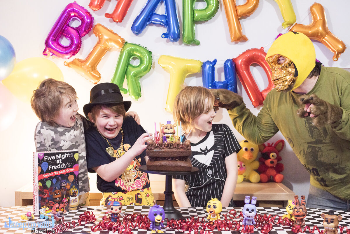 Image shows three boys enjoying the Five Nights at Freddy's Party table. There are Pop Vinyl Funko FNAF figures, a chocolate cake on a black pedestal and the Five Nights at Freddy's Board game, Survive 'til 6am.  A man dressed up with a metallic skull mask and wolf paw gloves is pretending to scare them from the right hand side of the image. Image by Keep up with the jones family.