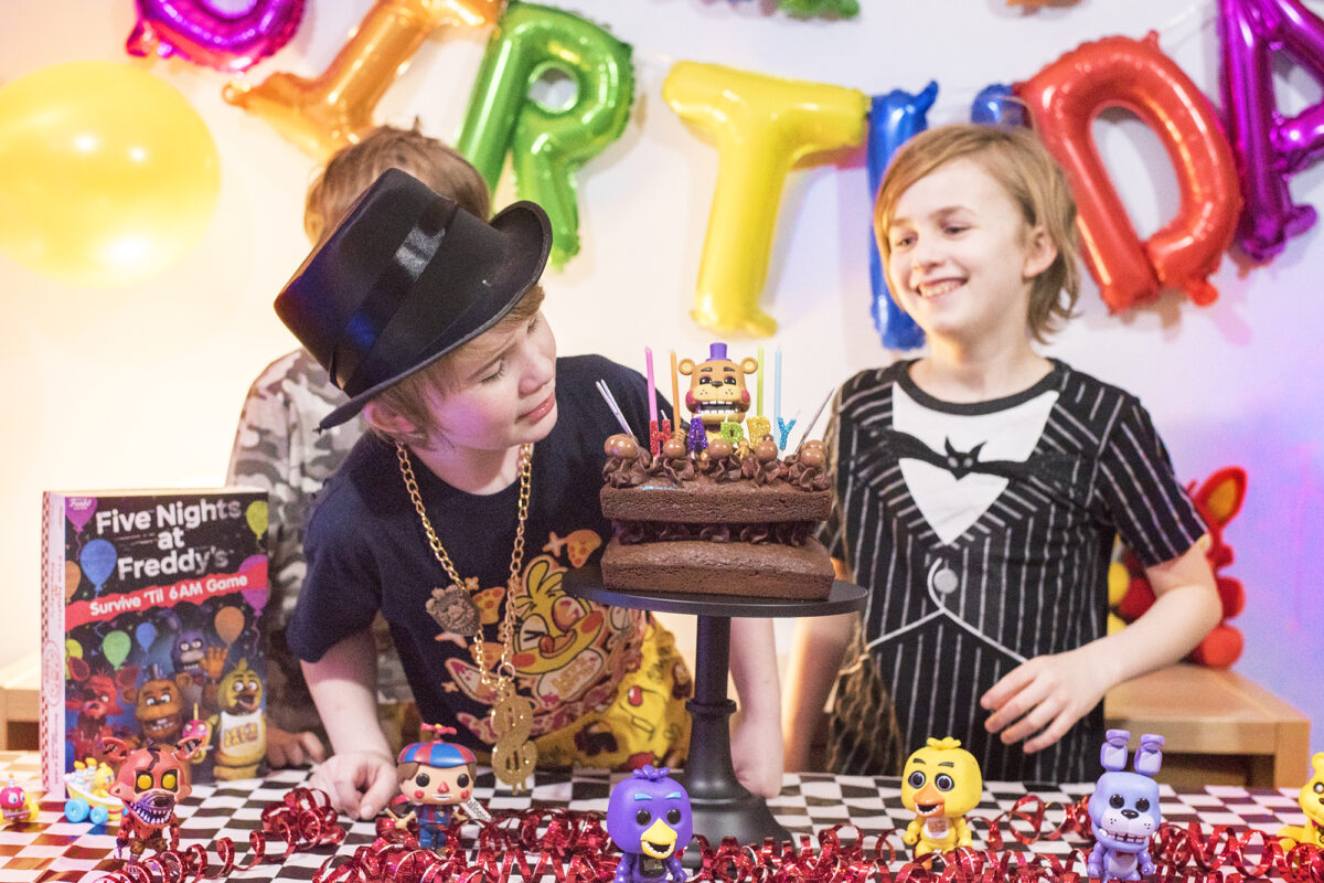 Image shows three boys enjoying the Five Nights at Freddy's Party table. There are Pop Vinyl Funko FNAF figures, a chocolate cake on a black pedestal and the Five Nights at Freddy's Board game, Survice 'til 6am. Image by Keep up with the jones family.