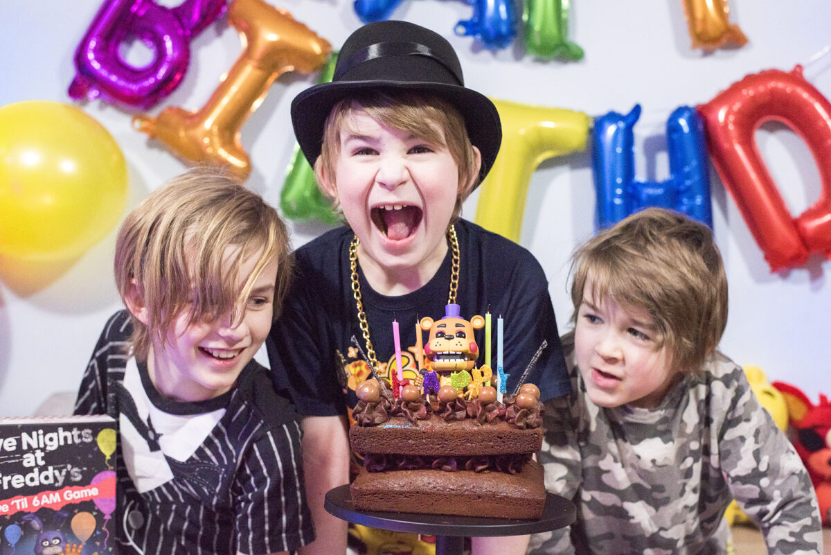Image shows three boys enjoying the Five Nights at Freddy's Party table. There are Pop Vinyl Funko FNAF figures, a chocolate cake on a black pedestal and the Five Nights at Freddy's Board game, Survive 'til 6am. Image by Keep up with the jones family. The middle boy is pretending to take a bit bite of the cake and the other two are smiling.