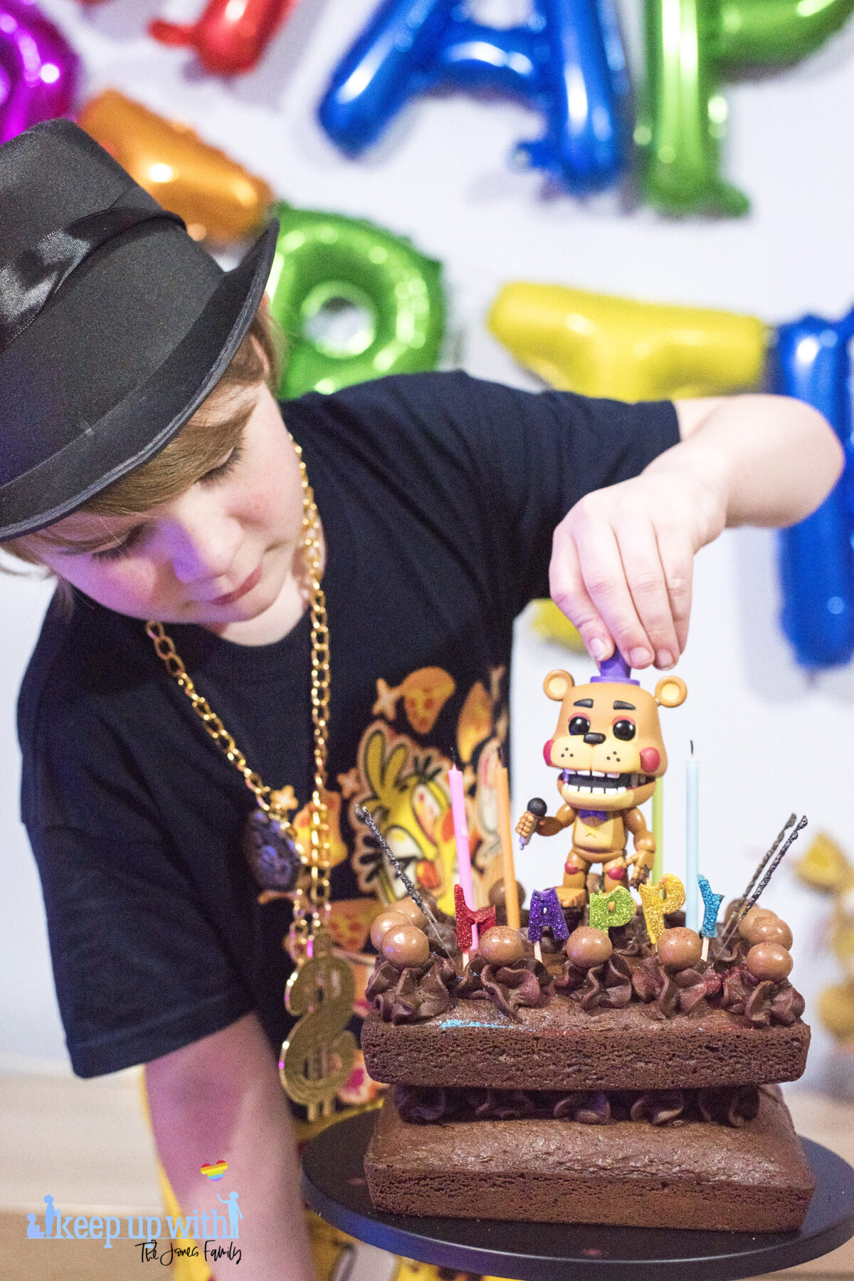 Image shows a blond haired boy wearing a black FNAF chica t-shirt and black top hat with a gold chain.   He is peering over a chocolate cake. He is lifting a Freddy Fazbear's Funko Pop Vinyl figure from Five Nights at Freddy's off the cake.