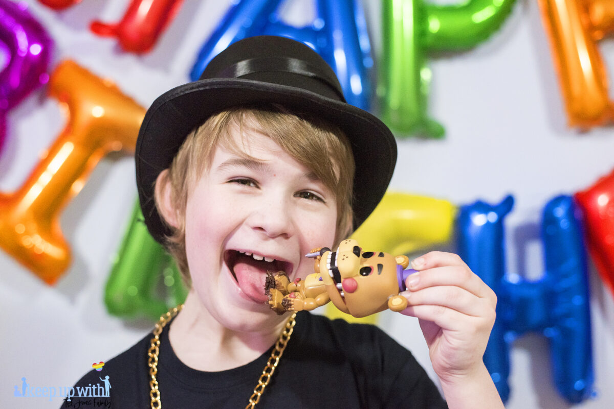 Image shows a blond haired boy wearing a black FNAF chica t-shirt and black top hat with a gold chain.   He is pretending to lick the chocolate cake off Freddy Fazbear's Funko Pop Vinyl figure from Five Nights at Freddy's which is covered in chocolate frosting from the cake. Image by keep up with the jones family.