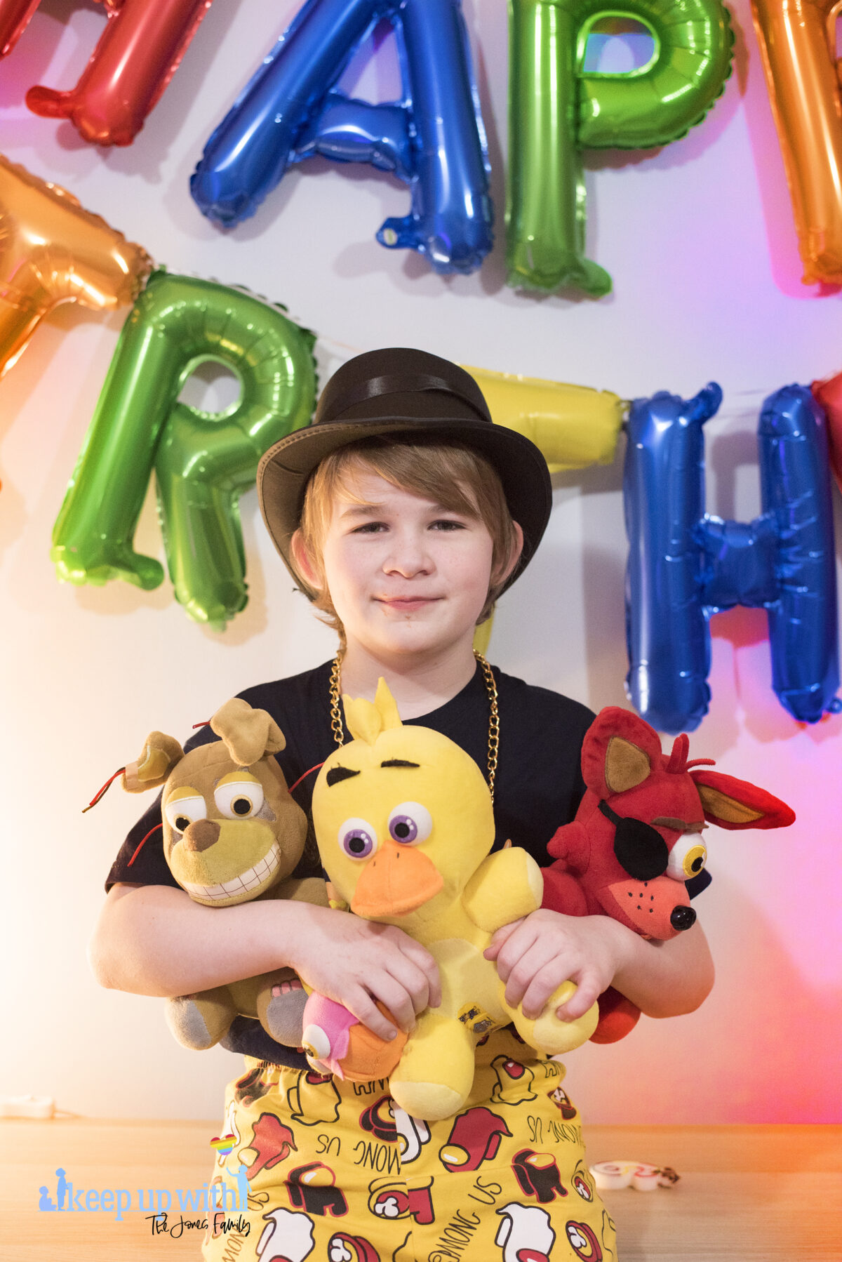 Image shows a blond haired boy with a black tshirt and top hat like Henry Stickman stood with three Five Nights at Freddy's large plush toys. Foxy, Chica and Springtrap. They are sat on a wooden sideboard against a pale blue wall and the coloured happy birthday balloons are on the wall in the background. Image by keep up with the jones family.