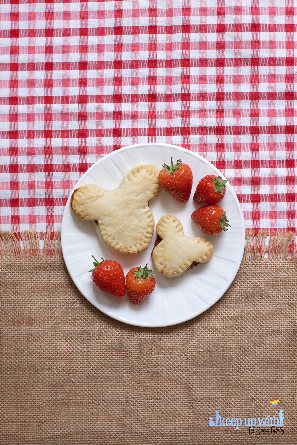 Image shows a flatlay of a red gingham checked tablecloth, overlaid with a jute burlap material with a fringe. On top is a white Vera Wang sideplate with two Mickey Mouse shaped shortcrust pies on. One is larger than the other, and there are strawberries next to the pies. There is a ShopDisney fork balancing on the plate with a summer citrus and apples pattern on it.  The image is watermarked by Keep up with the Jones Family.