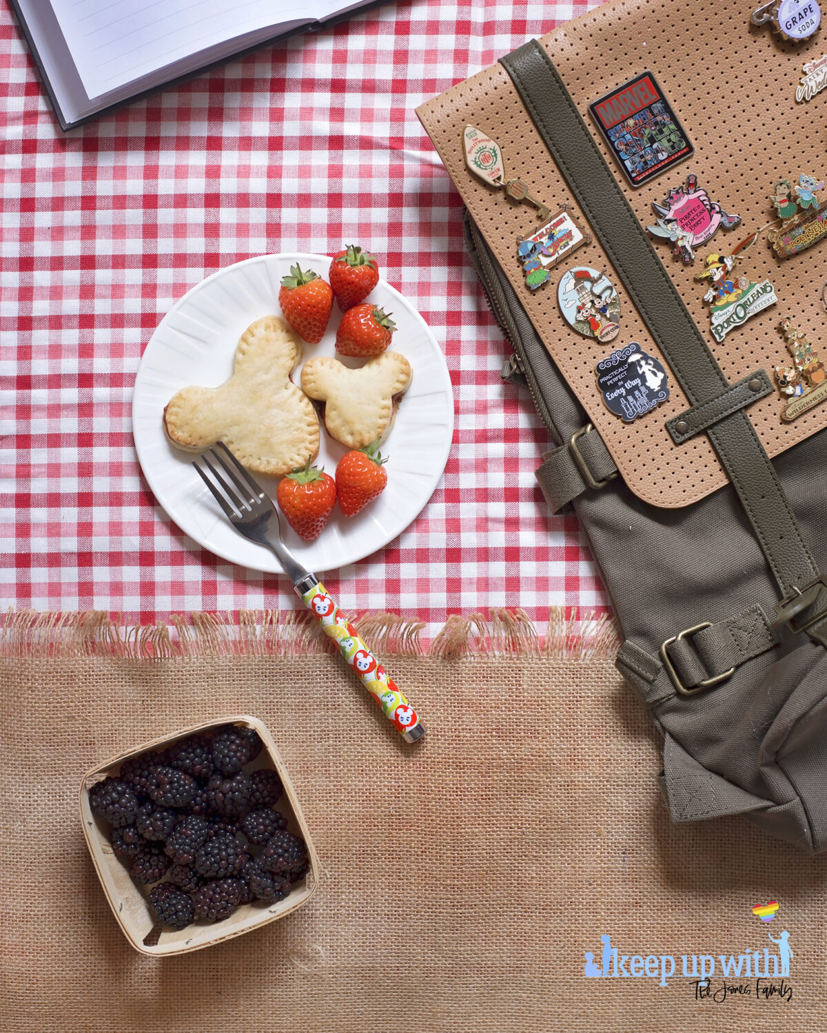 Image shows a flatlay of a red gingham checked tablecloth, overlaid with a jute burlap material with a fringe. On top is a ShopDisneyUK rucksack with many Disney pins from Disney's fairytale weddings, Port Orleans, Castaway Cay, Disneyland Hotel, Cinderellas Table and many more. Next to the bag is a white Vera Wang sideplate with two Mickey Mouse shaped shortcrust pies on. One is larger than the other. There is a ShopDisney fork balancing on the plate with a summer citrus and apples pattern on it.  There is a wooden punnet of blackberries below the plate.The image is watermarked by Keep up with the Jones Family.