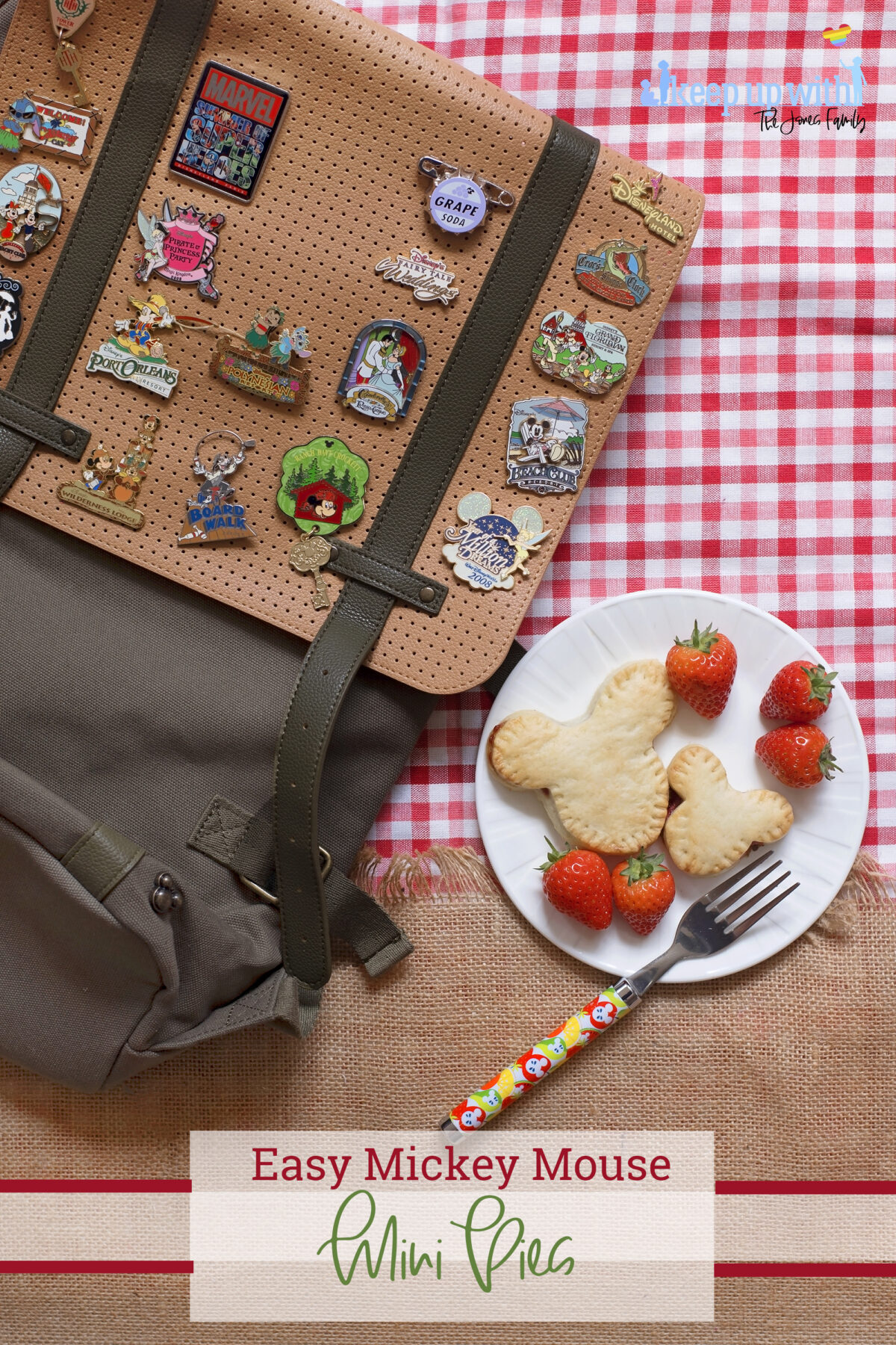 Image shows a flatlay of a red gingham checked tablecloth, overlaid with a jute burlap material with a fringe. On top is a ShopDisneyUK rucksack with many Disney pins from Disney's fairytale weddings, Port Orleans, Castaway Cay, Disneyland Hotel, Cinderellas Table and many more. Next to the bag is a white Vera Wang sideplate with two Mickey Mouse shaped shortcrust pies on. One is larger than the other. There is a ShopDisney fork balancing on the plate with a summer citrus and apples pattern on it.  The image is watermarked by Keep up with the Jones Family.