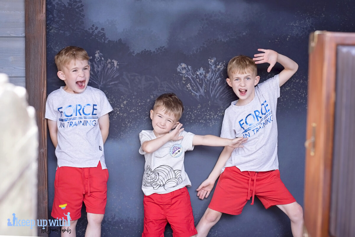 Image shows three little boys dressed in red shorts and star wars t-shirts posing in the Disneyland Paris Spirit Photography Booth where you can print a personalised copy of the Mysterious Chronicle by Phantom Manor. Image by Keep Up With The Jones Family.