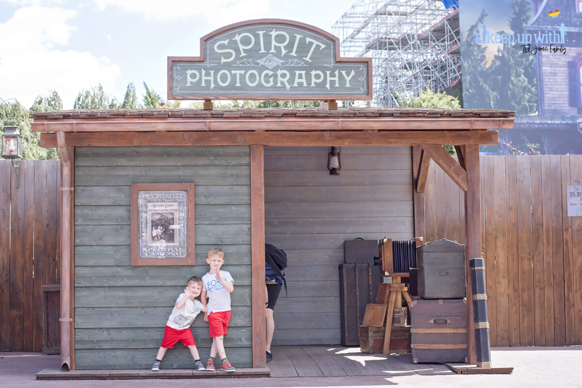 Image shows the Disneyland Paris Spirit Photography Booth in Frontierland and two little boys from the Jones Family dressed in red shorts stood outside smiling.  Image by Keep Up With the Jones Family.