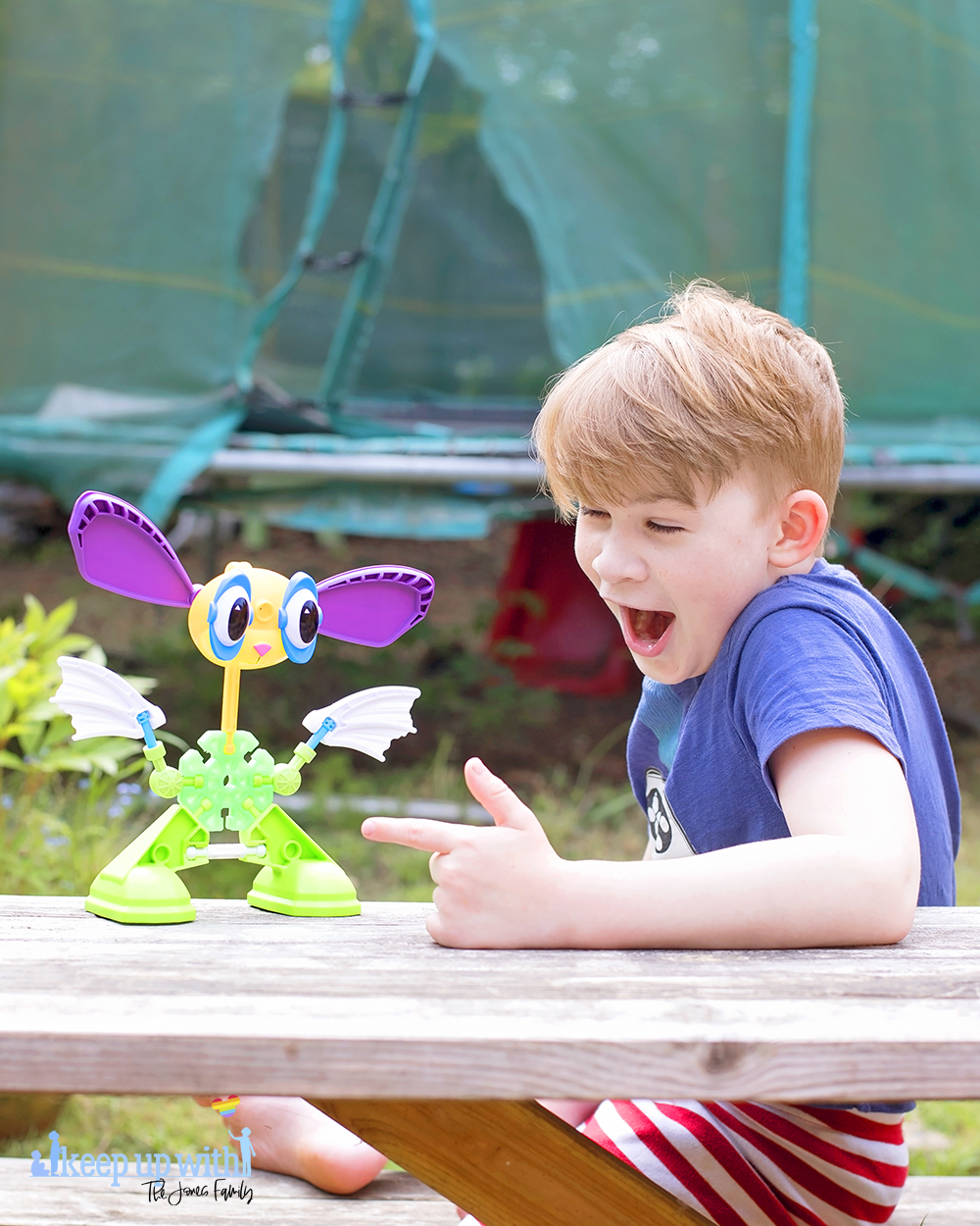 Image shows a boy with blond hair sat at a picnic table, pointing at a toy in front of him.  On the wooden picnic table in front of them is a rabbit like creature, which is made from pieces of the Kid K'nex Budding Builders construction toys box from Basic Fun UK.  By Keep Up With The Jones Family.