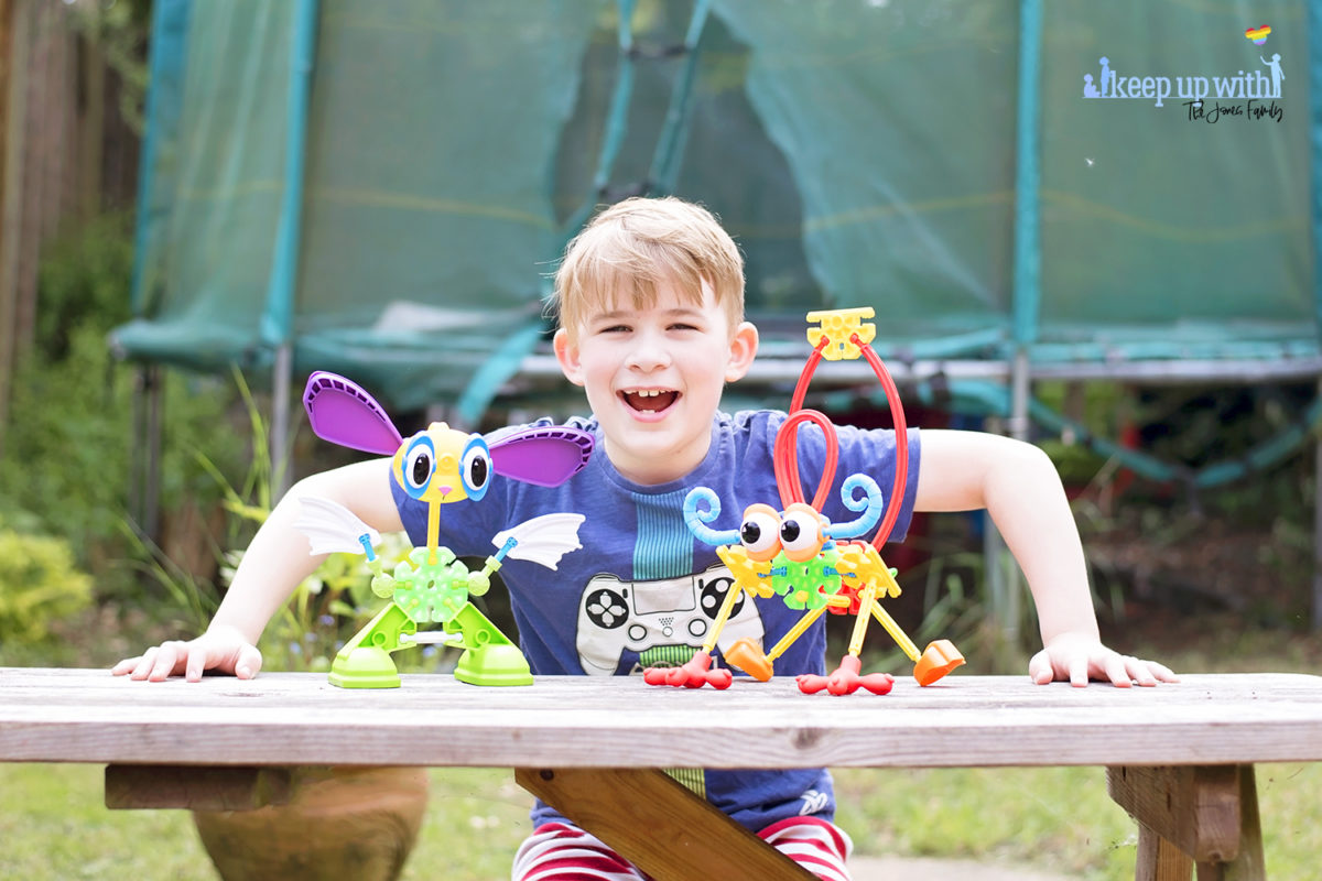 Image shows a boy smiling with his arms on a wooden picnic table in the garden.  On the wooden picnic table in front of him are two creatures which are made from pieces of the Kid K'nex Budding Builders construction toys box from Basic Fun UK.  By Keep Up With The Jones Family.