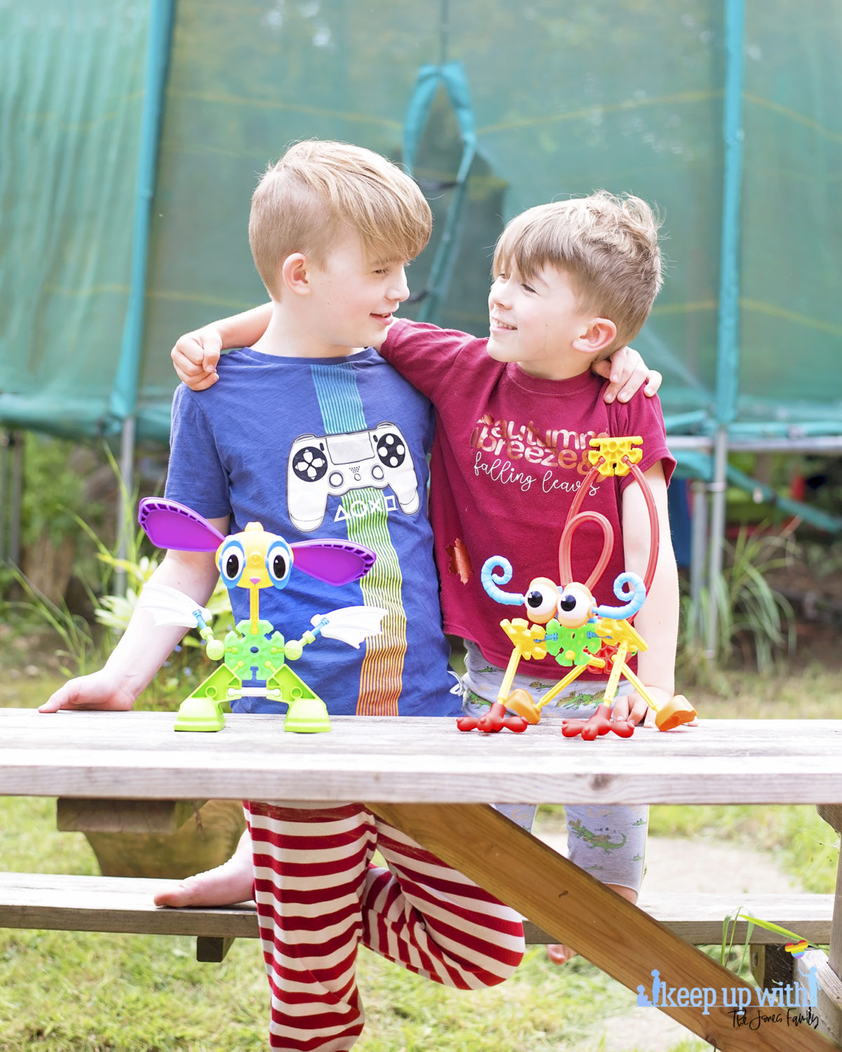 Image shows two boys with their arm around each other's shoulders, looking at each other.  On the wooden picnic table in front of them are two creatures which are made from pieces of the Kid K'nex Budding Builders construction toys box from Basic Fun UK.  By Keep Up With The Jones Family.