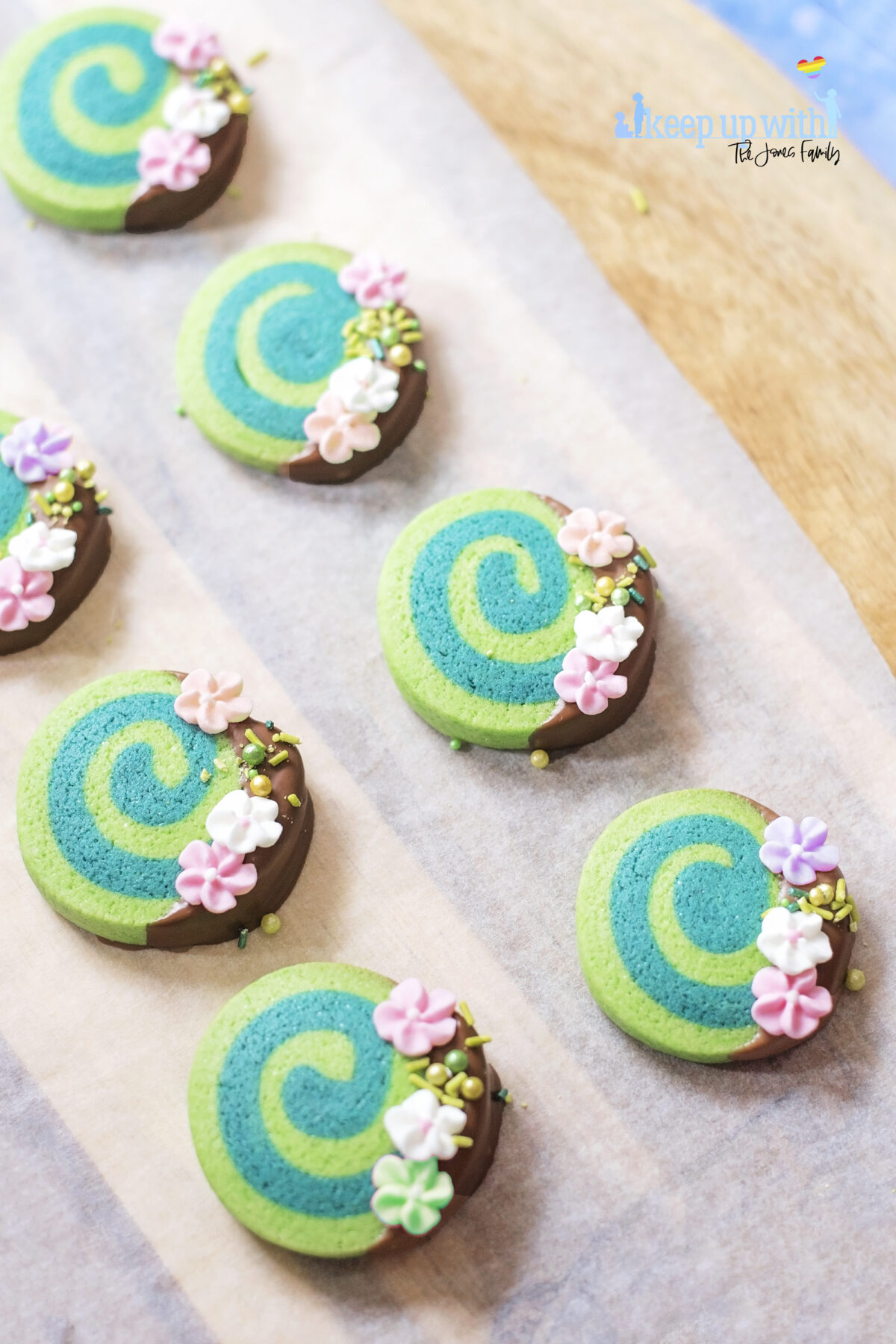Image shows Disney's Moana Heart of Te Fiti Biscuits, a swirl of bright and dark green, dipped slightly in milk chocolate and embellished with sugar blossom flowers and green sprinkles.  They are set on a light wood chopping board with baking paper underneath. . Image by keep up with the jones family.