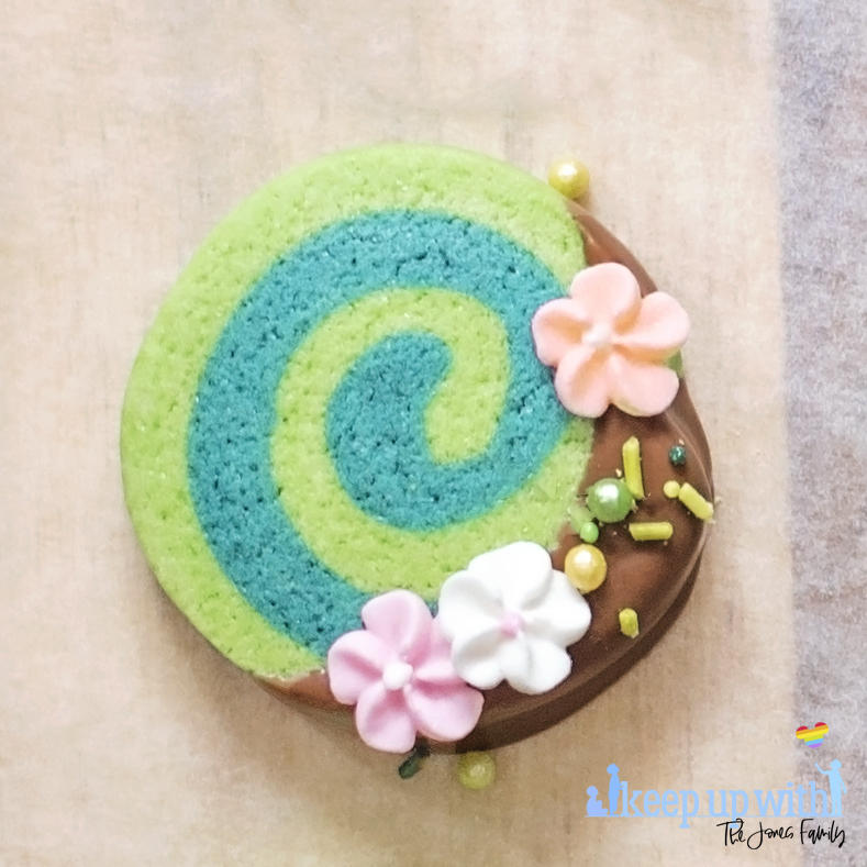 Image shows one of Disney's Moana Heart of Te Fiti Biscuits, a swirl of bright and dark green cookie, dipped slightly in milk chocolate and embellished with sugar blossom flowers and green sprinkles.  They are set on a light wood chopping board with baking paper underneath. . Image by keep up with the jones family.