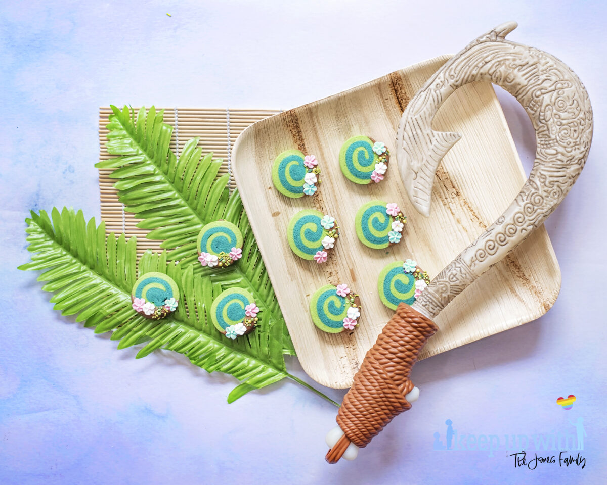 Image shows Disney's Moana Heart of Te Fiti Biscuits, a swirl of bright and dark green cookie, dipped slightly in milk chocolate and embellished with sugar blossom flowers and green sprinkles.  They are set on a bamboo plate with a fern underneath, and a bamboo sushi rolling mat is laid underneath. Maui's fish hook is resting on the plate also. Image by keep up with the jones family.