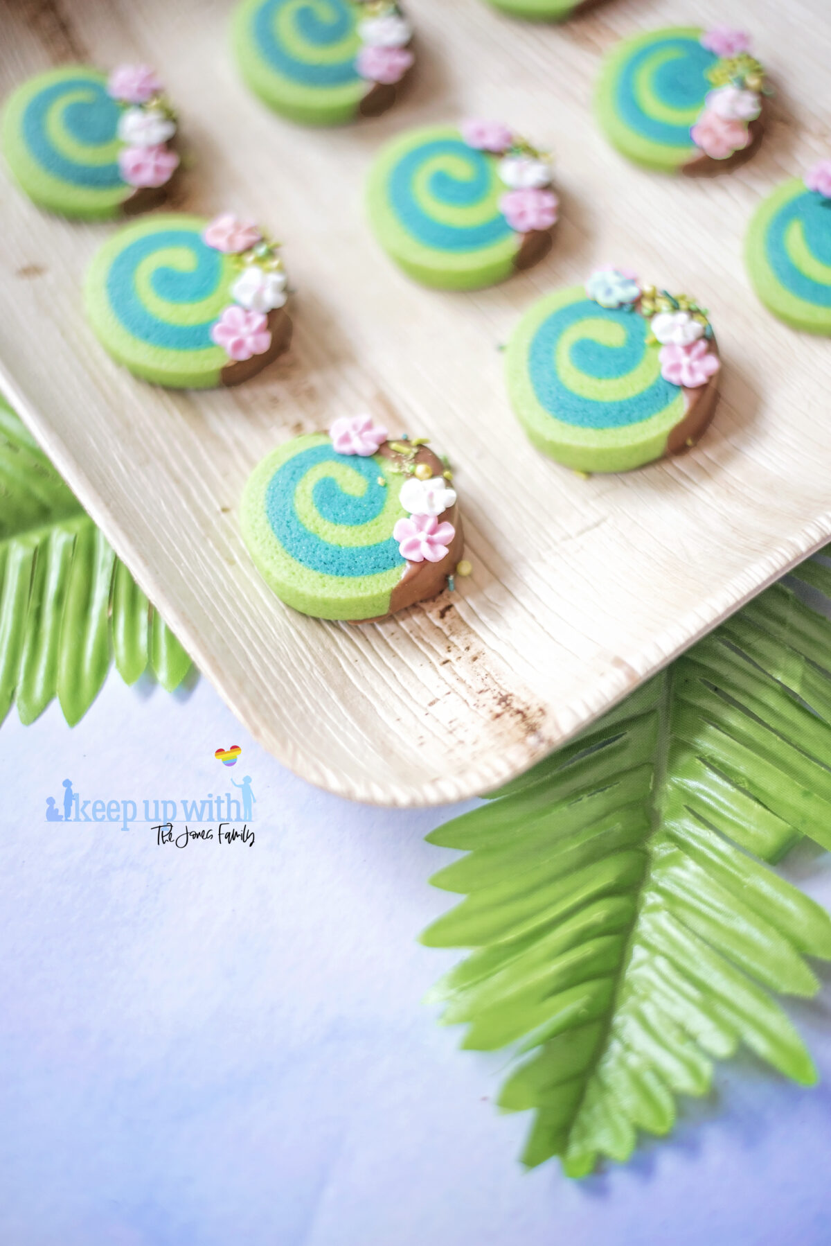 Image shows how to make Disney's Moana Heart of Te Fiti Biscuits, a swirl of bright and dark green, dipped slightly in milk chocolate and embellished with sugar blossom flowers and green sprinkles.  They are set on a bamboo plate with a fern underneath.  Image by keep up with the jones family.