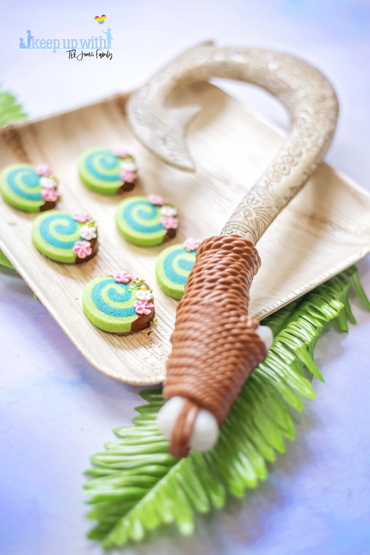 Image shows Disney's Moana Heart of Te Fiti Biscuits, a swirl of bright and dark green, dipped slightly in milk chocolate and embellished with sugar blossom flowers and green sprinkles. They are set on a bamboo plate with a fern underneath, and Maui's fish hook is resting on the plate also. Image by keep up with the jones family.