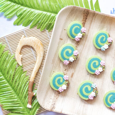 Image shows how to make Disney's Moana Heart of Te Fiti Biscuits, a swirl of bright and dark green, dipped slightly in milk chocolate and embellished with sugar blossom flowers and green sprinkles. They are set on a bamboo plate with a fern underneath, and a small toy version of Maui's fish hook is resting next to the plate also. Image by keep up with the jones family.