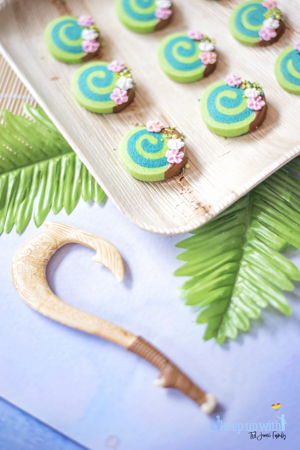 Image shows how to make Disney's Moana Heart of Te Fiti Biscuits, a swirl of bright and dark green, dipped slightly in milk chocolate and embellished with sugar blossom flowers and green sprinkles.  They are set on a bamboo plate with a fern underneath, and Maui's fish hook is resting on the plate also. Image by keep up with the jones family.