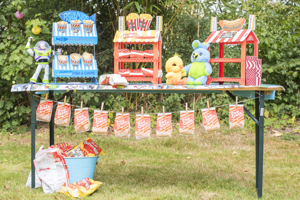 Image shows a party table outdoors in a field. The table has three novelty food stands on top; fish and chips, popcorn and hot dogs. Ducky and Bunny plushies from Disney's Toy Story 4 are sat on the table and underneath the table is a string of popcorn bags pegged for guests at the party.  Buzz Lightyear hangs off the edge of the table.