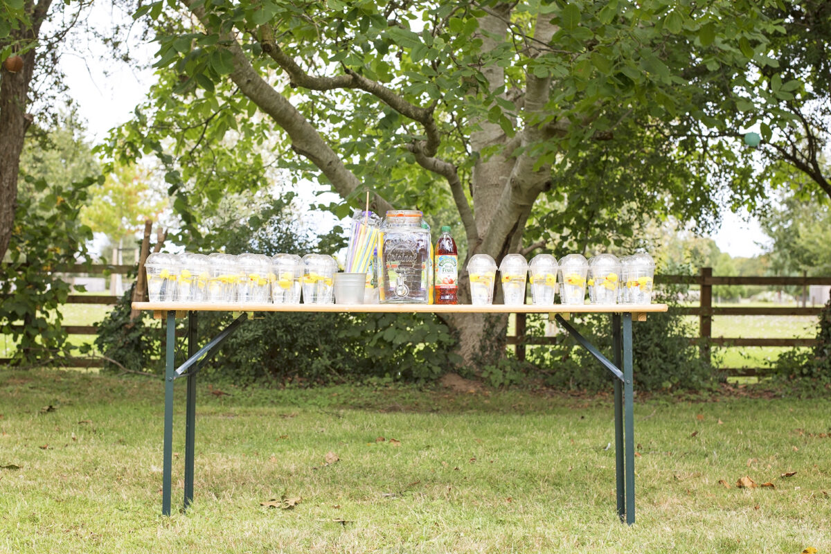 Image shows a party table under a tree in the shade. Atop of it are rows and rows of clear plastic cups with dome shaped lids, each filled with water and a yellow rubber duck.  There is a tin of coloured straws, squash bottles and a large mason drinks dispenser filled with water.