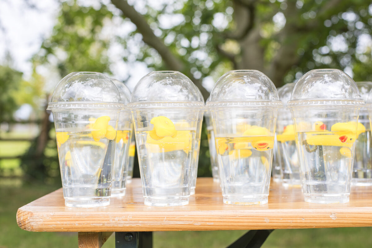 Image shows a table covered in rows of clear domed water cups with lids, filled with water. Each cup has a miniature yellow rubber duck floating in it.