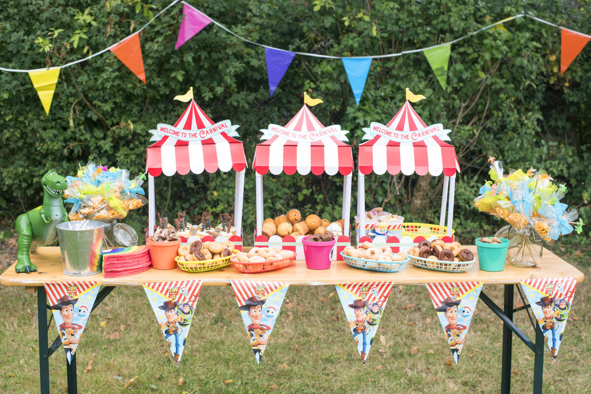 Image Shows a Toy Story party themed table outside in a garden.  There are three cardboard food stands in the shape of red and white big tops, which read welcome to the carnival. On the corner of the table is Disney's Rex from Toy Story toy and there are rainbow napkins, toy story bunting and the table is covered in Toy Story Army soldier cupcakes, mini donuts in different flavours, mini muffins, crackers and biscuits.