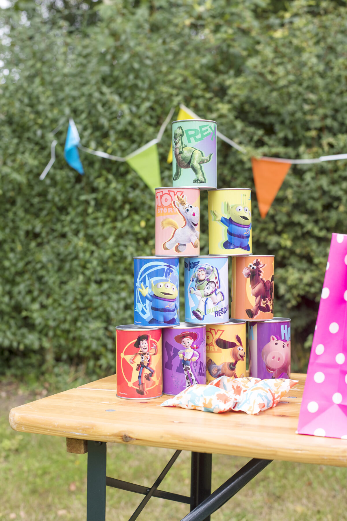 Image shows a wooden party table outside with a Toy Story themed set of knock down cans and bean bags in bright colours.  The table is outdoors in a field.