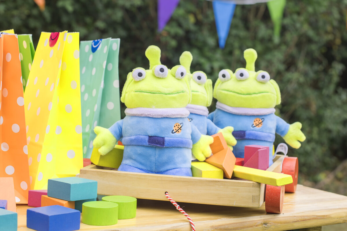 Image shows three plush Toy Story Alien toys from shopdisneyuk on top of a party table, sat with brightly coloured wooden blocks and party bags.