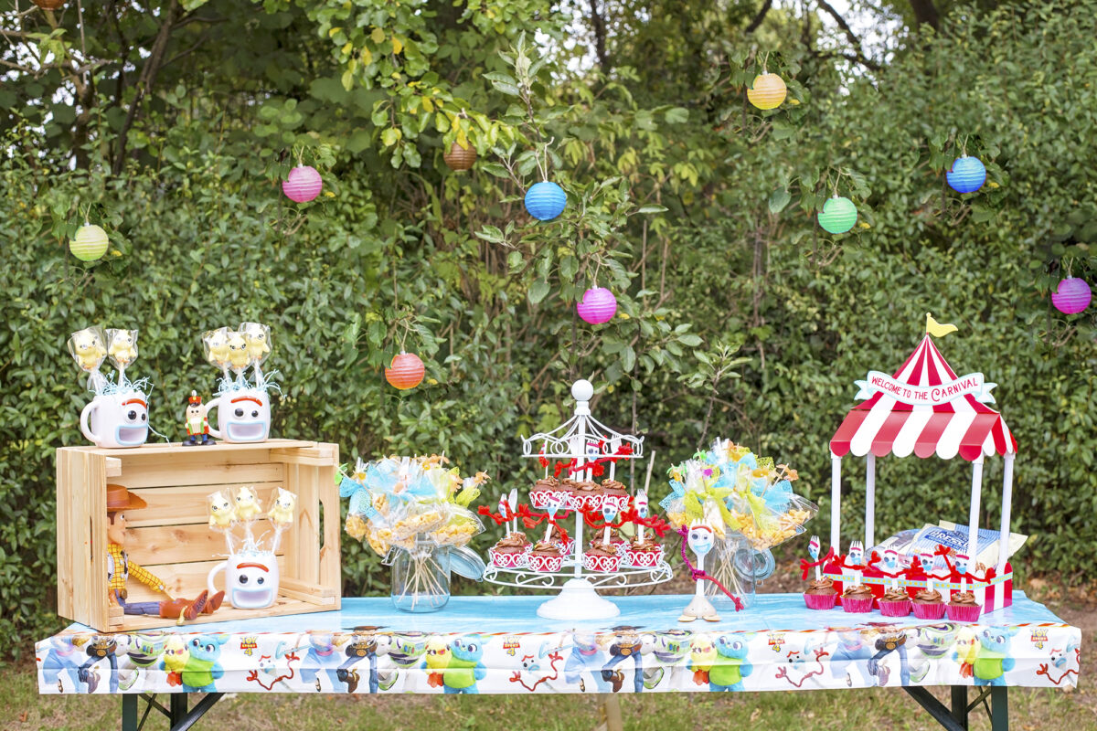 Image shows a party table outdoors in a field with a backdrop of hedges covered with coloured paper lanterns.  On the party table are carnival decorations, and Woody the Cowboy from Disney's Toy Story. There are mugs in the shape of Forky from Toy Story 4 which are filled with cake pops in the shape of Ducky from the film.  A Forky toy sits on the table next to a miniature food tent which says welcome to the carnival. There is a carousel for cupcakes filled with forky cupcakes, and bags of pepperidge farm goldfish crackers on fishing poles  in glass jars with little plastic goldfish sat on top.