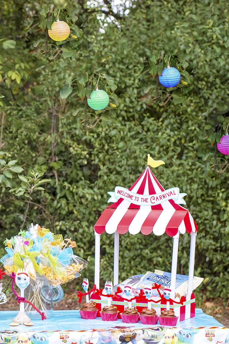 Image shows a party table set in a carnival theme with Disney's Toy Story Forky figure sitting next to a red and white striped carnival big top table decoration filled with pretzels and forky cupcakes lined along the front.