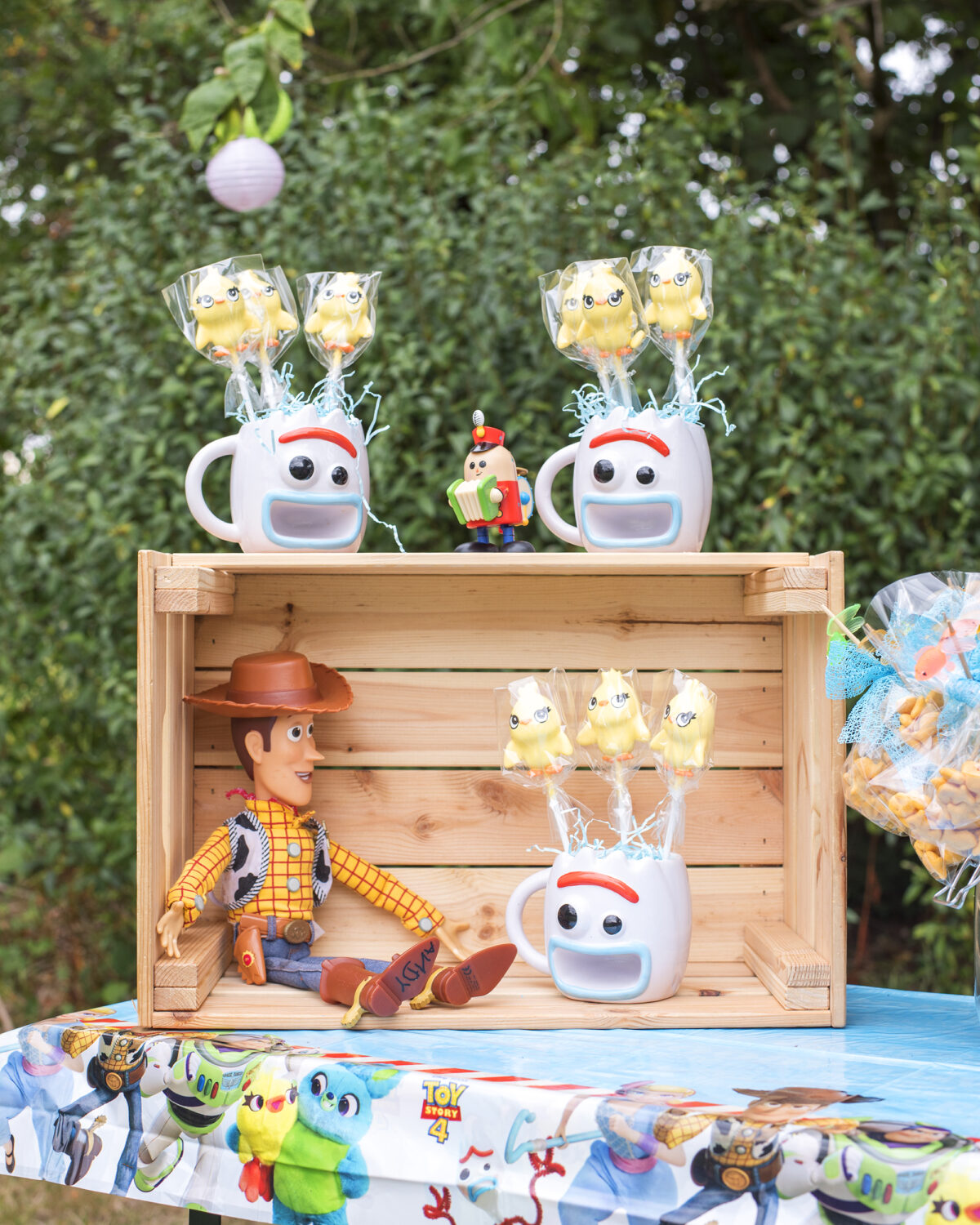 Image shows a party table with an upturned wooden ikea crate. Inside the crate sits a toy of Woody the Cowboy from Disney's Toy Story, and on top are three Forky shaped mugs filled with Ducky shaped cake pops. The original toy story pixar tinker toy is on top of the crate.