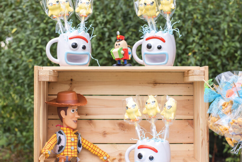 How to host a toy story party: Image shows a party table with a toy story tablecloth and wooden crate perched on top. Woody the Disney Cowboy toy sits inside the crate and three mugs in the shape of the face of Forky from Toy Story Four are sat on and in the crate. Inside the mugs are Ducky cake pops. The table is outdoors at a toy story party.