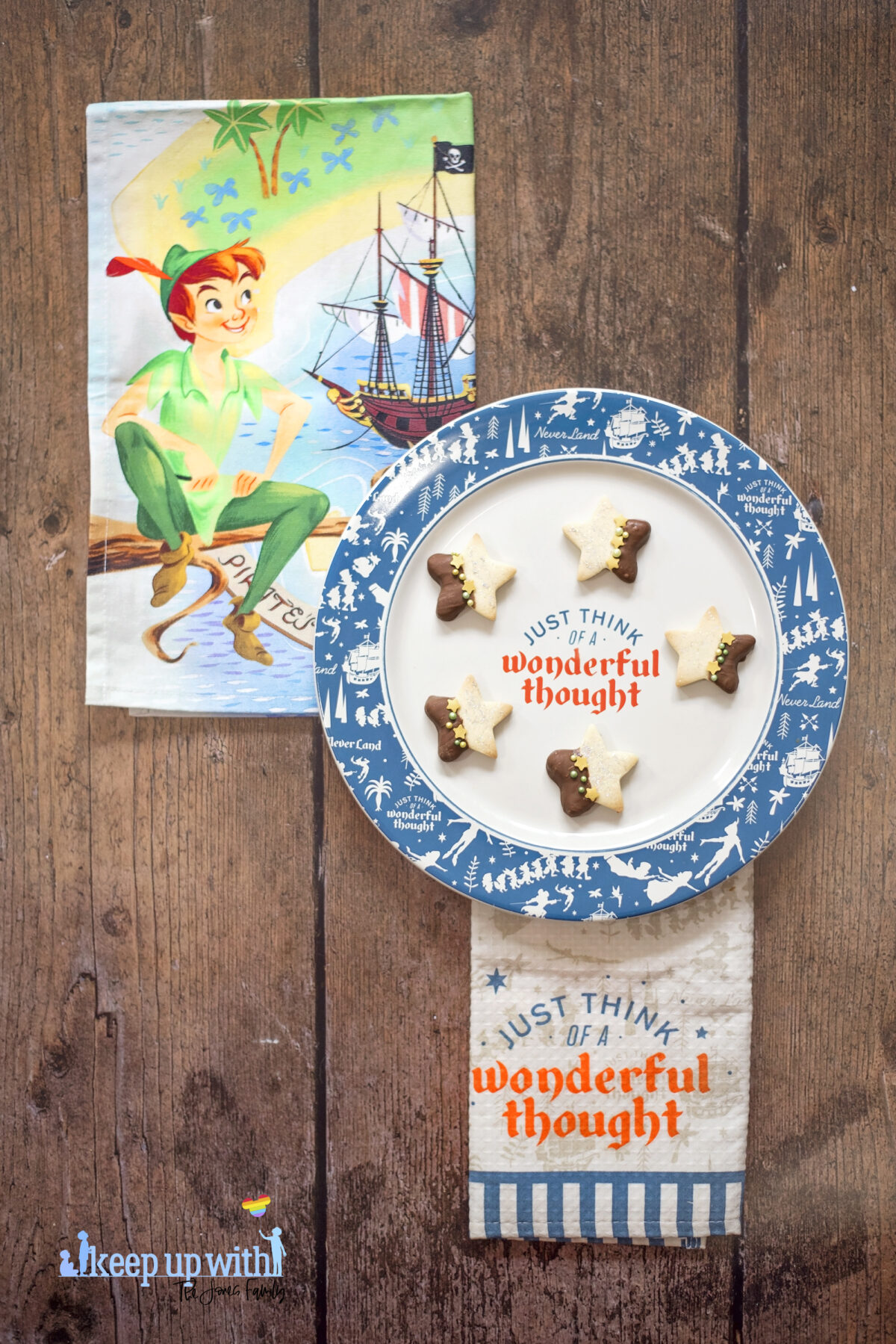 """Image shows a wooden tabletop with ShopDisneyUK's Peter Pan tea towel set and a Peter Pan dinner plate reading """"just think of a wonderful thought"""" on it.  On the Disney plate are small star shaped biscuits half of each Peter Pan Second Star to the Right Biscuit is dipped in chocolate and  the other is sprinkled with silver edible glitter.  The dividing line is decorated with yellow star sprinkles and green pearl shaped sprinkles. Image by Keep Up With The Jones Family"""