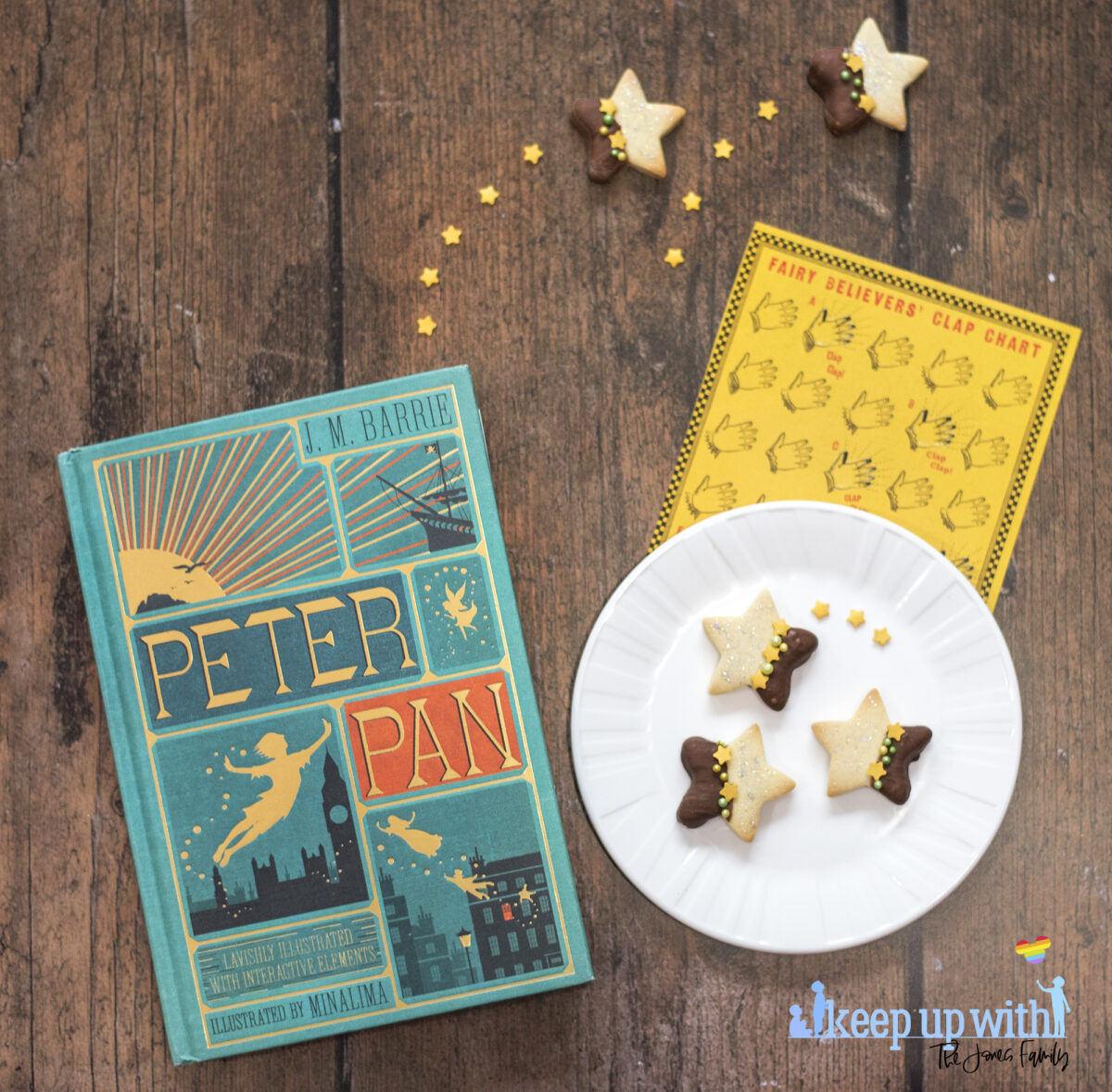 Image shows a wooden tabletop with a copy of J M Barrie's Peter Pan, a small white Vera Wang Wedgewood plate and a fairy clapping chart,  On the table are small star shaped biscuits. Half of each Peter Pan Second Star to the Right Biscuit is dipped in chocolate and  the other is sprinkled with silver edible glitter.  The dividing line is decorated with yellow star sprinkles and green pearl shaped sprinkles. Image by Keep Up With The Jones Family