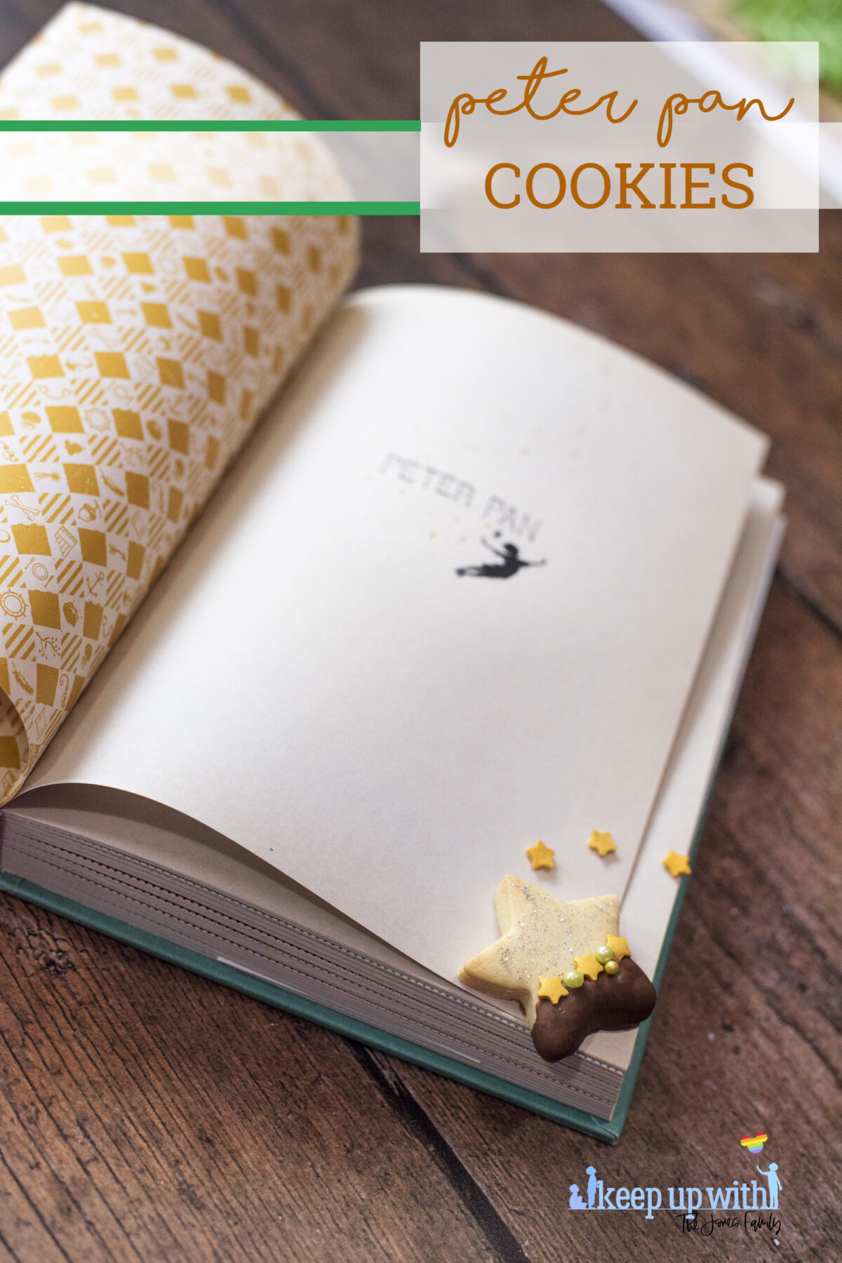 Image shows a wooden tabletop with a copy of J M Barrie's Peter Pan open. On the book pages and the table are small star shaped biscuits. Half of each biscuit is dipped in chocolate and  the other is sprinkled with silver edible glitter.  The dividing line is decorated with yellow star sprinkles and green pearl shaped sprinkles. Image by Keep Up With The Jones Family