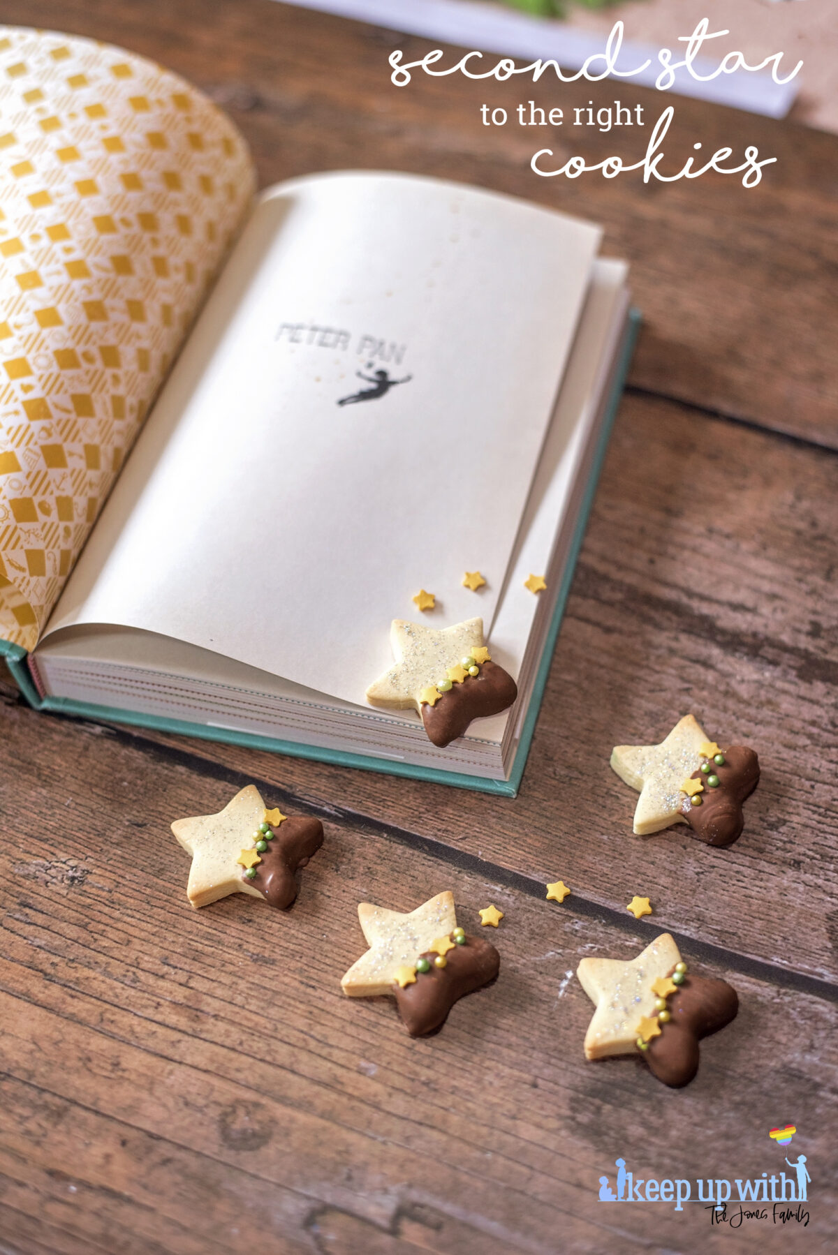 Image shows a wooden tabletop with a copy of J M Barrie's Peter Pan open. On the book pages and the table are small star shaped biscuits. Half of each Peter Pan Second Star to the Right biscuit is dipped in chocolate and  the other is sprinkled with silver edible glitter.  The dividing line is decorated with yellow star sprinkles and green pearl shaped sprinkles. Image by Keep Up With The Jones Family