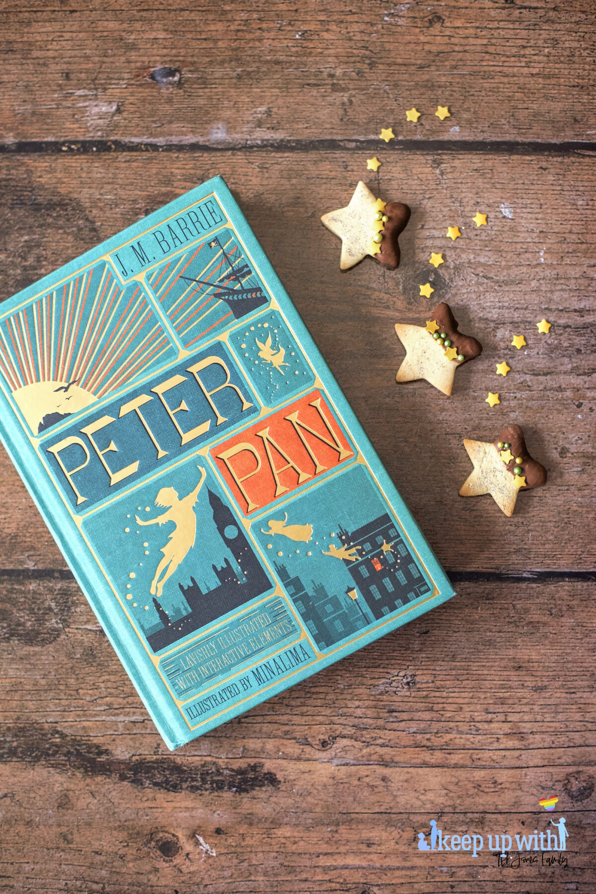 Image shows a wooden tabletop with a copy of J M Barrie's Peter Pan. On the book pages and the table are small star shaped biscuits. Half of each biscuit is dipped in chocolate and  the other is sprinkled with silver edible glitter.  The dividing line is decorated with yellow star sprinkles and green pearl shaped sprinkles. Image by Keep Up With The Jones Family