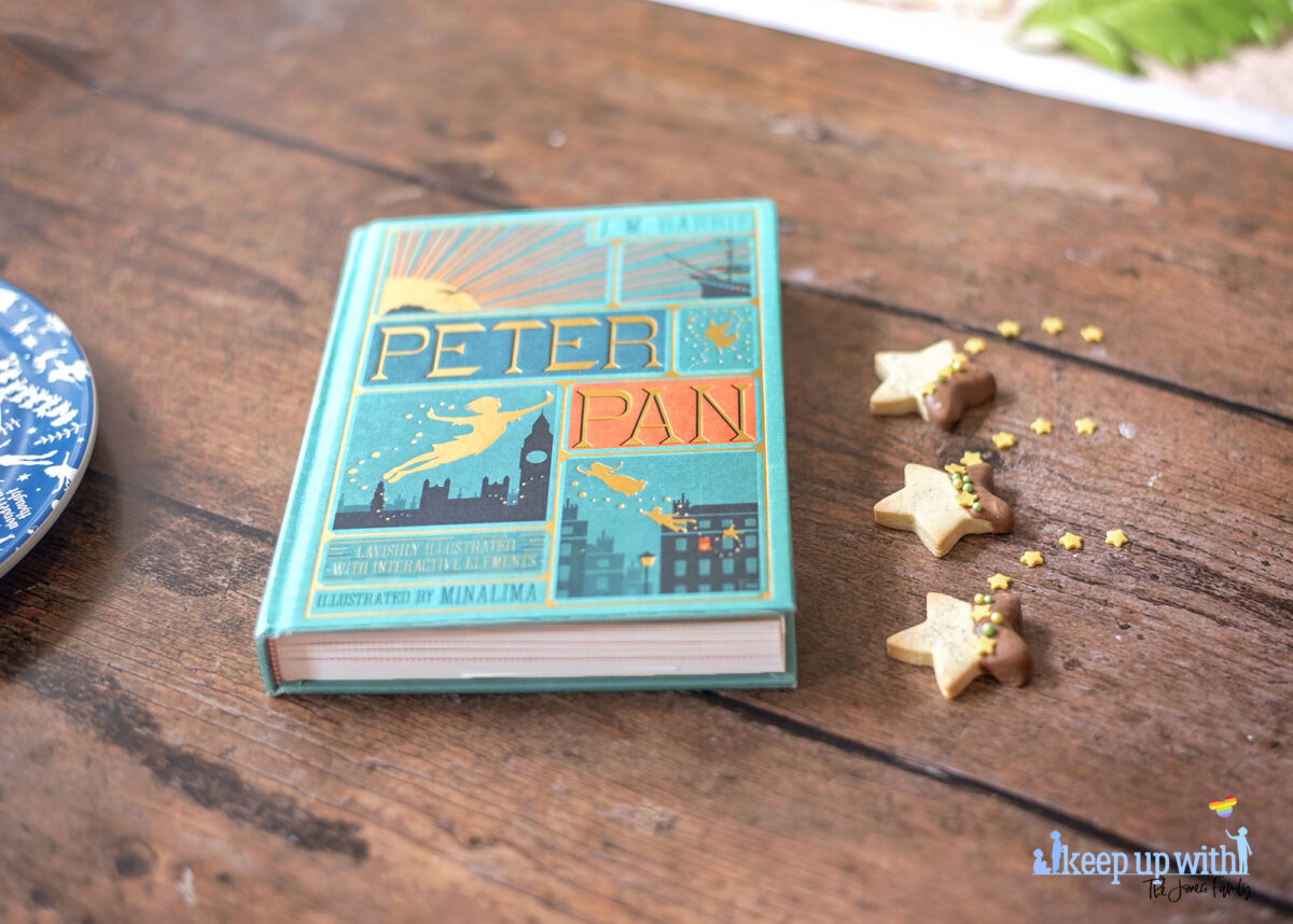 Image shows a wooden tabletop with a copy of J M Barrie's Peter Pan. On the book pages and the table are small star shaped biscuits. Half of each Peter Pan Second Star to the Right Biscuit is dipped in chocolate and  the other is sprinkled with silver edible glitter.  The dividing line is decorated with yellow star sprinkles and green pearl shaped sprinkles. Image by Keep Up With The Jones Family