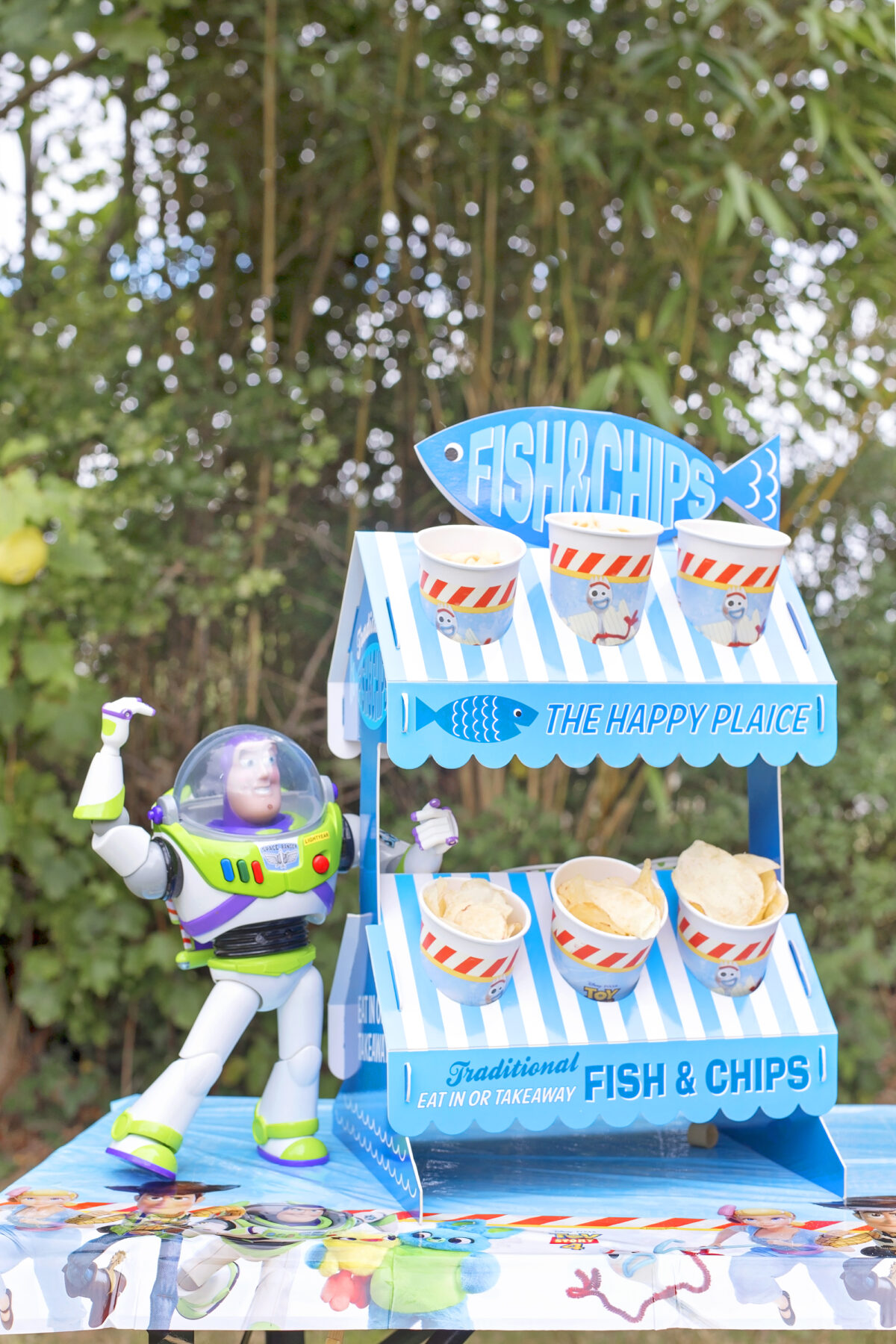 Image shows a party table outdoors with Disney's Buzz Lightyear toy stood on top of it, next to a novelty fish and chip stand made from cardboard.
