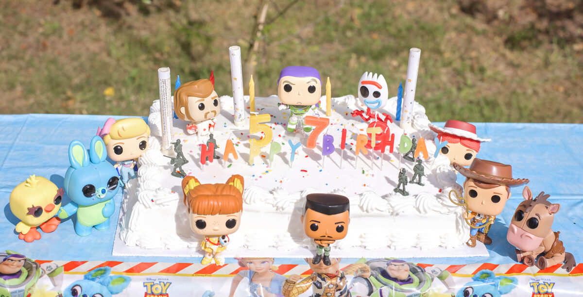 Image shows a semi birds eye view, angled to see the top of a large white Costco cake covered in Toy Story 4 Pop Funko toys.  Combat Carl, Woody, Bullseye, Gabby, Bunny and Ducky, Buzz, Jessie, Forky and Duke kaboom can be seen.