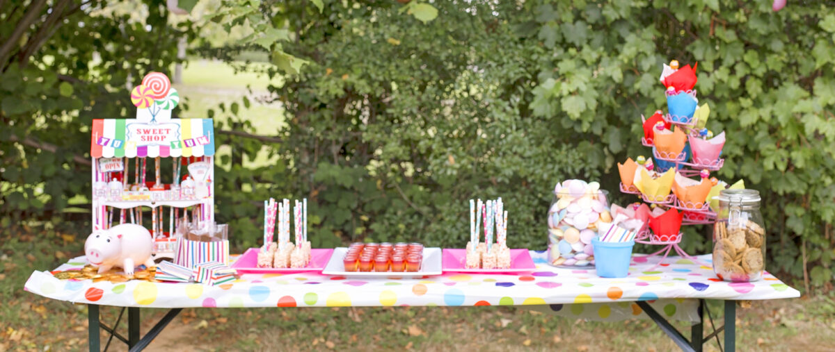 Image shows a party table set with rainbow jellies, brightly coloured chocolate cupcakes with lollipops, a jar of chocolate chip cookies, rice krispie lollipops covered in rainbow sprinkles, and a little sweet shop stand filled with chocolate dipped marshmallows. A Hamm ceramic money box from Disney's Toy Story 4 is on the table sat on top of a mountain of gold chocolate coins.  The table is outdoors at the party in a field with hedges behind it.
