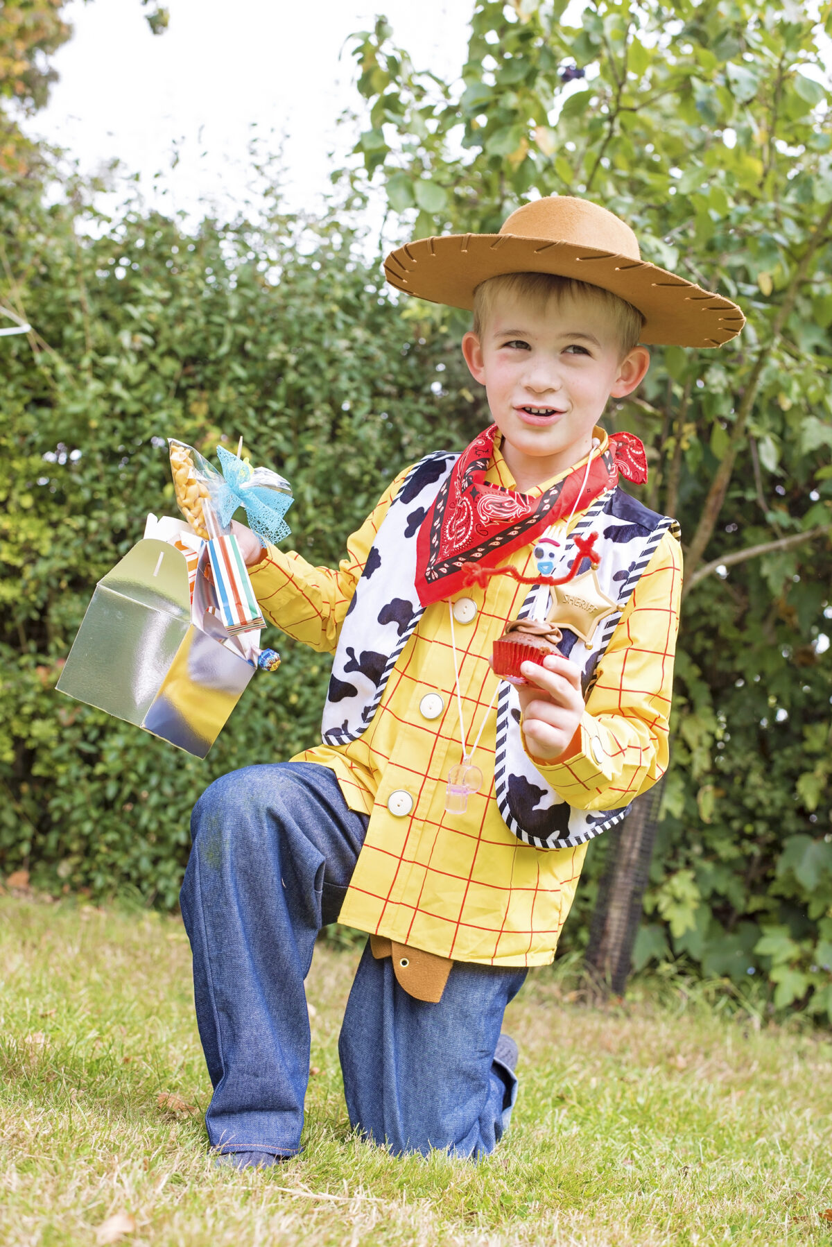 Image shows a member of the Jones Famiily dressed as Woody from Disney's Toy Story and holding a Forky cupcake in one hand and a lunchbox themed for Office Giggles McDimples in the other hand.