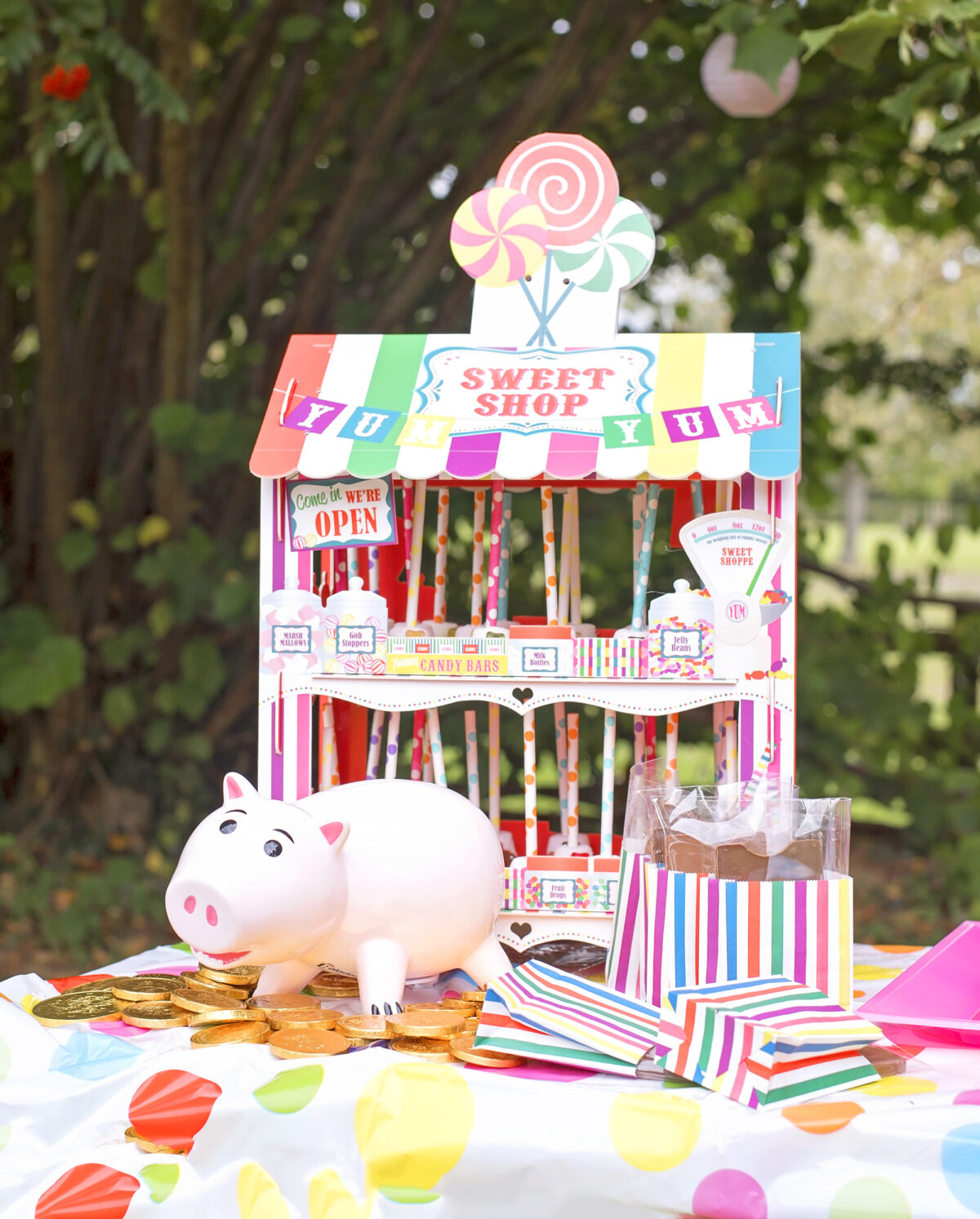 Image shows a ceramic piggy bank in the shame of Hamm from Disney's Toy Story sat on top of a mountain of gold chocolate coins. In the background is a novelty sweet stand filled with chocolate dipped marshmallow pops and in the foreground are chocolate carnival tickets.