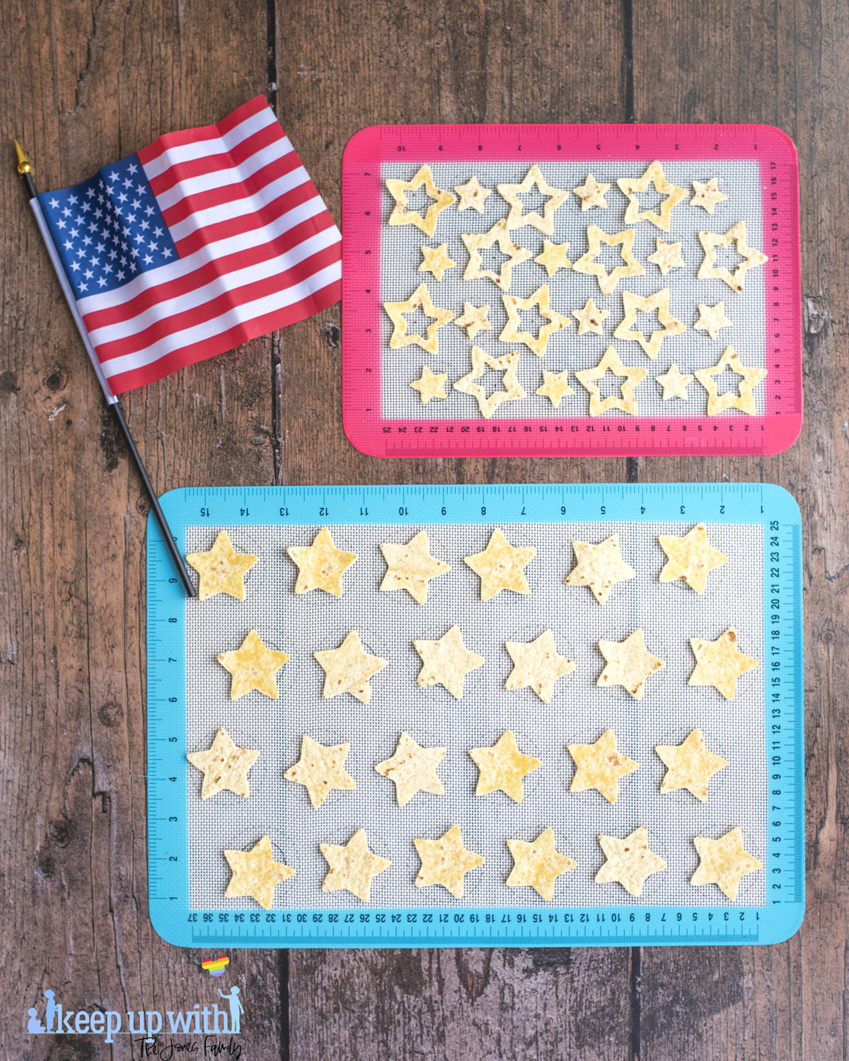 Image shows two silicone baking sheets on a dark wooden table. One is red and one is blue. On top of them are cut out star chips 'n' dip nachos from tortillas. The American flag is laid next to the baking sheets. Image by keep up with the jones family.