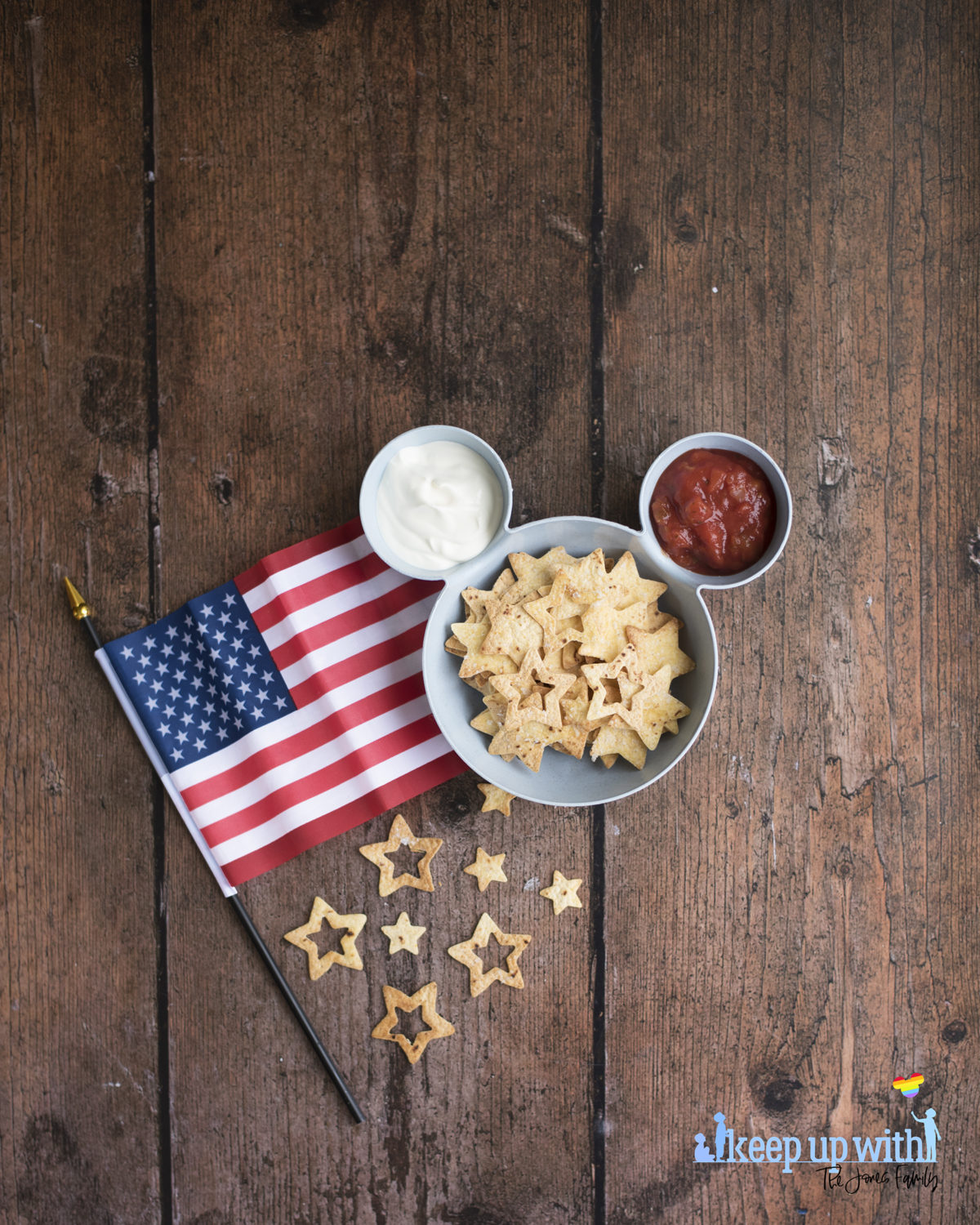 Image shows a blue bowl in the shape of Mickey Mouse suitable for chips 'n' dip. There is an American flag laid close to the bowl on the dark wooden table.  Inside the bowl is tomato salsa, soured cream, and star spangled nacho chips. Image by keep up with the jones family.