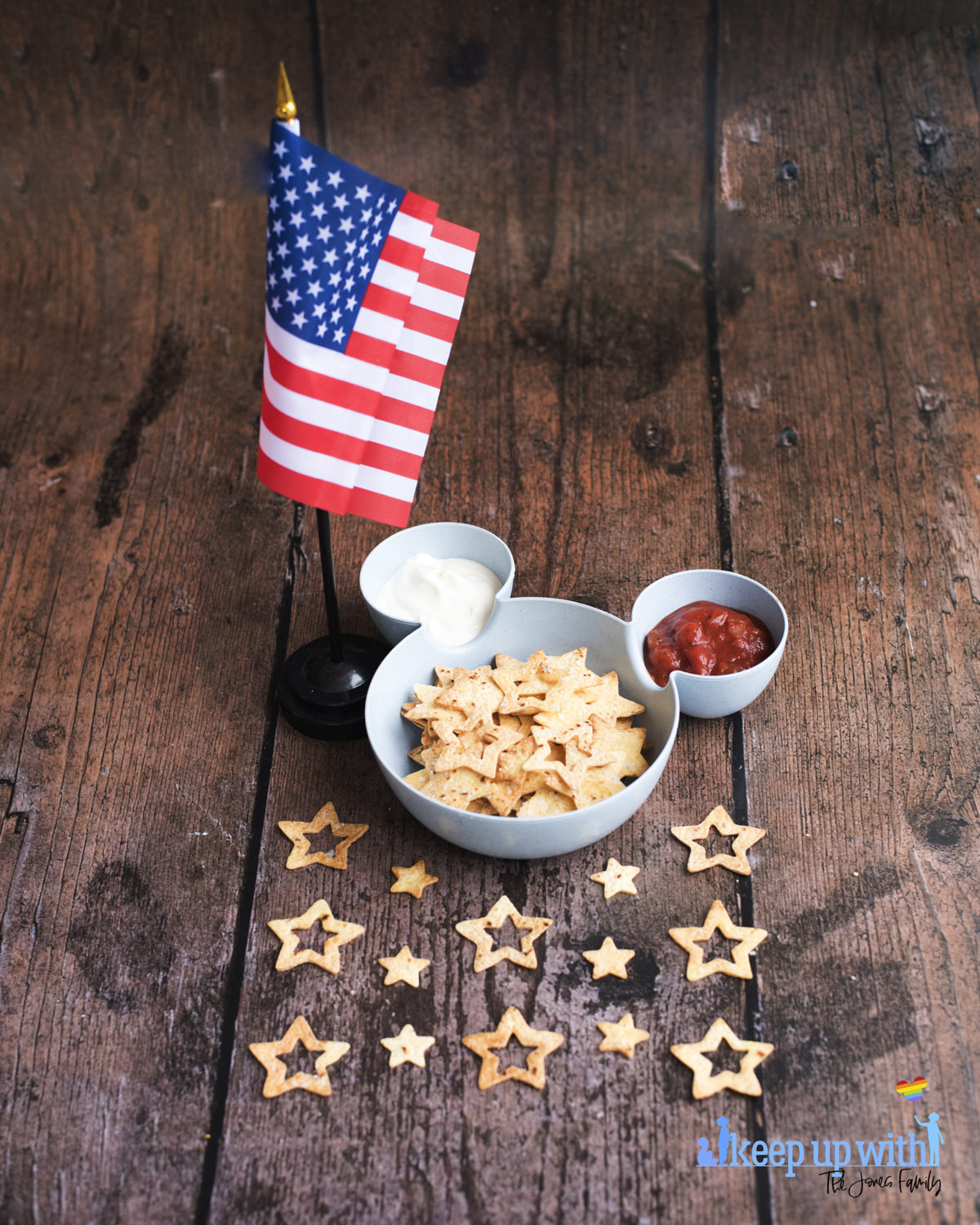 Image shows a blue bowl in the shape of Mickey Mouse suitable for chips and dip. There is an American flag stood close to the bowl and inside the bowl is tomato salsa, soured cream, and star spangled nacho chips. Image by keep up with the jones family.